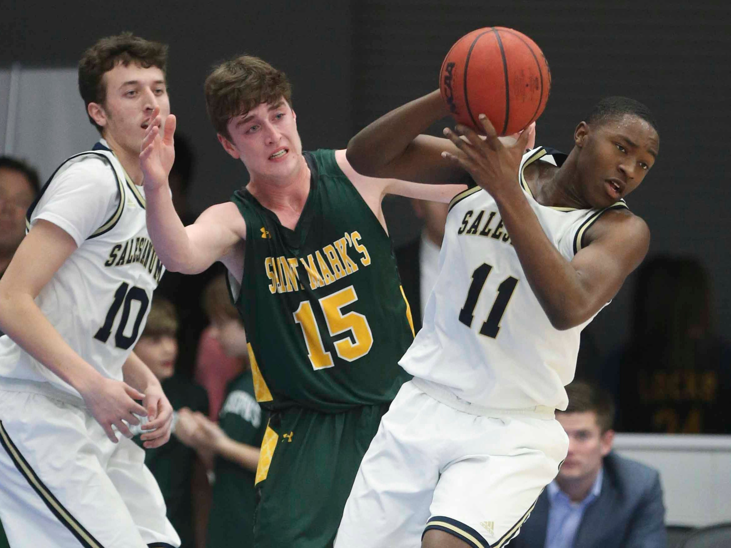 Salesianum's Jack Brown (left) and Darnell Vaughn (11) work against St. Mark's Victor Marcelo in the SL24 Memorial Basketball Classic at the 76ers Fieldhouse in Wilmington Friday.