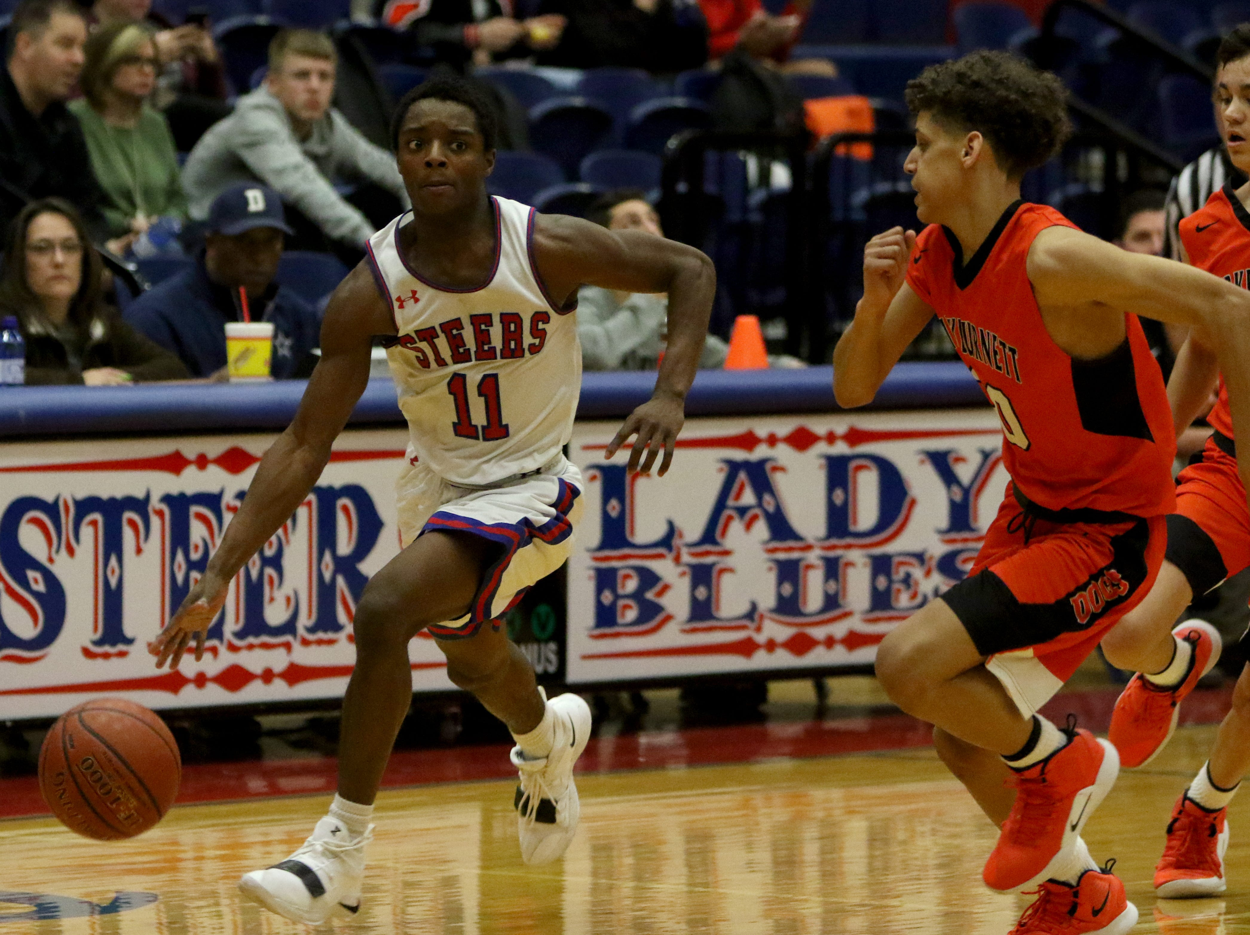 Graham's Marc Tate dribbles in the game against Burkburnett Friday, Feb. 8, 2019, in Graham. The Steers defeated the Bulldogs 75-70.