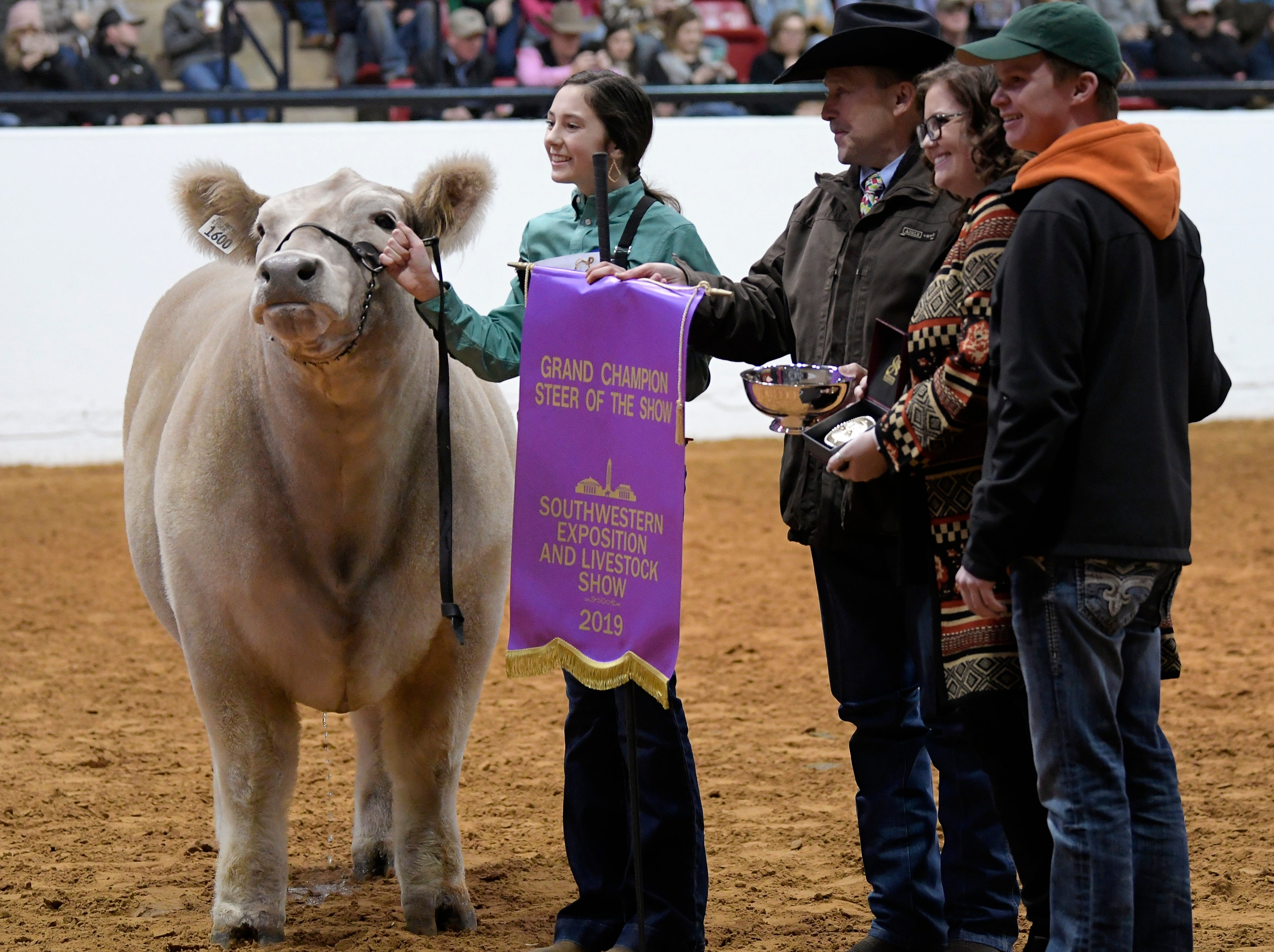 Aven Horn, left, holds a banner after her steer Bentley was named the Grand Champion steer of the Stock Show at Will Rogers Memorial Center in Fort Worth, Texas, Friday, Feb. 8, 2019.