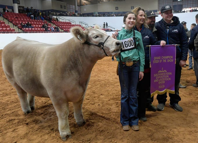 Aven Horn (1600) and family pose for a photo after Horn's steer Bentley, left, was named the Grand Champion steer of the Stock Show at Will Rogers Memorial Center in Fort Worth, Texas, Friday, Feb. 8, 2019.