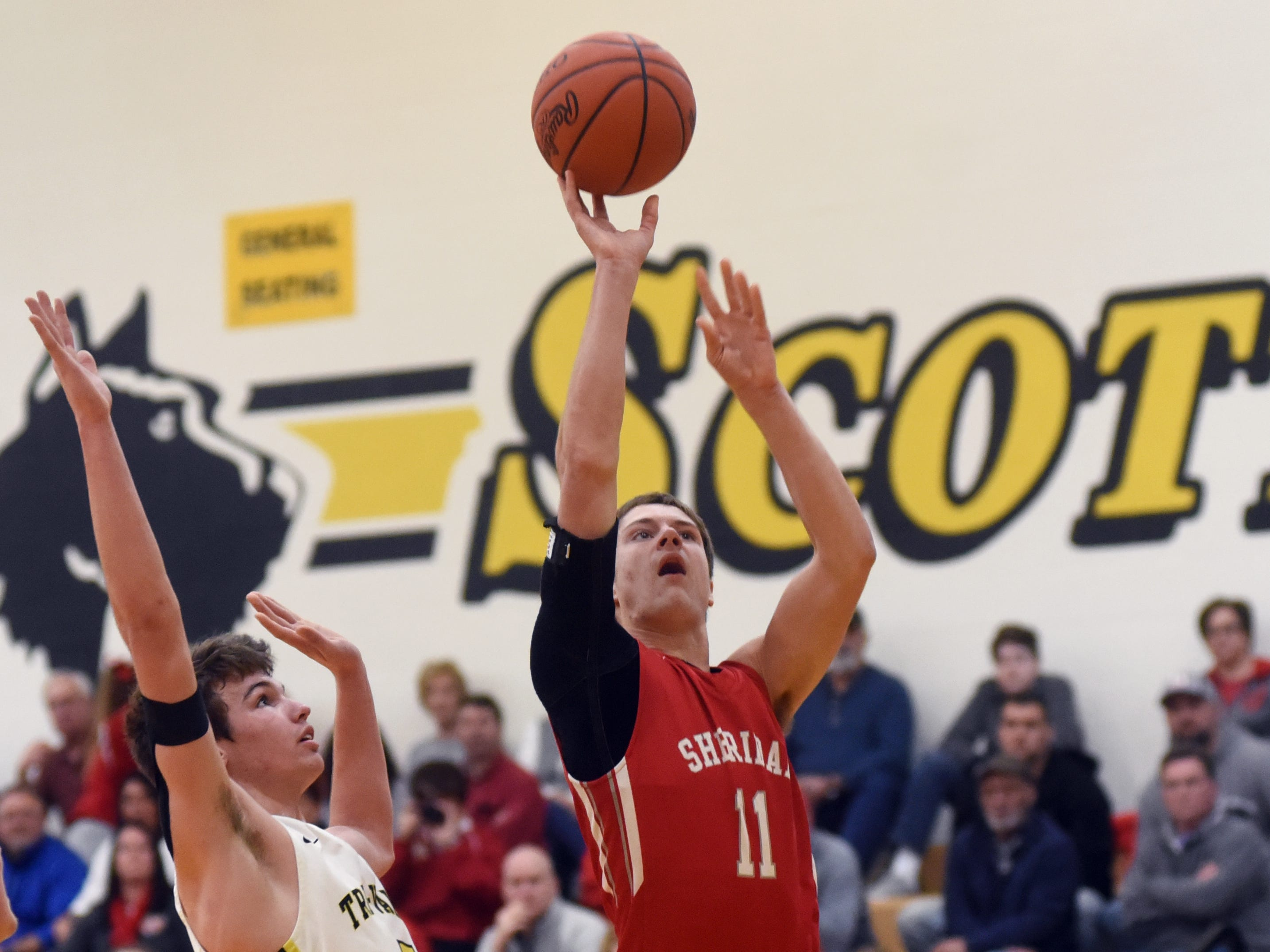Sheridan's Luken Hill takes a shot in the lane over Tri-Valley's Keaton Williams on Friday night in Dresden.