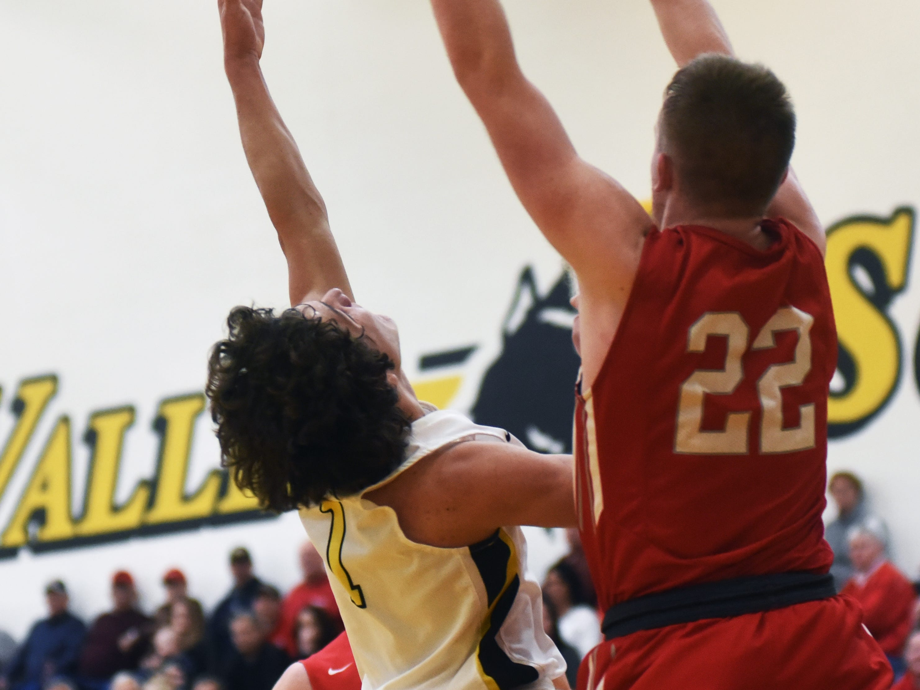 Tri-Valley's Ty Smith shoots an off-balanced layup over Sheridan's Landen Russell on Friday night in Dresden.