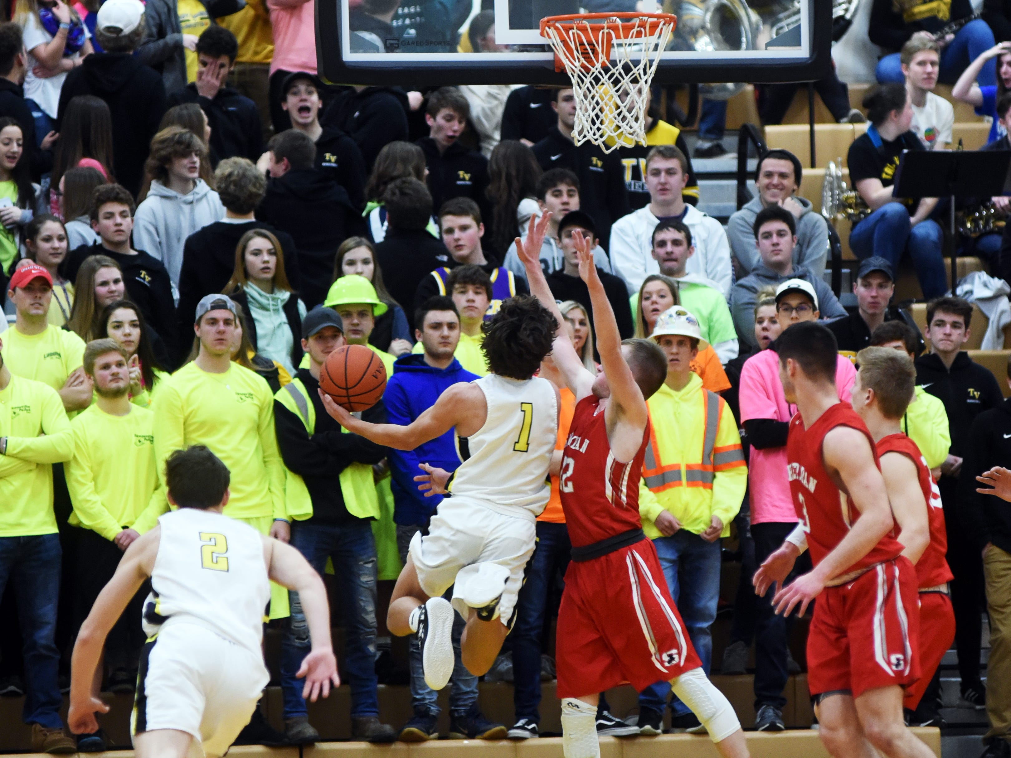 Tri-Valley's Ty Smith goes up in the lane against Sheridan's Landen Russell on Friday night in Dresden.