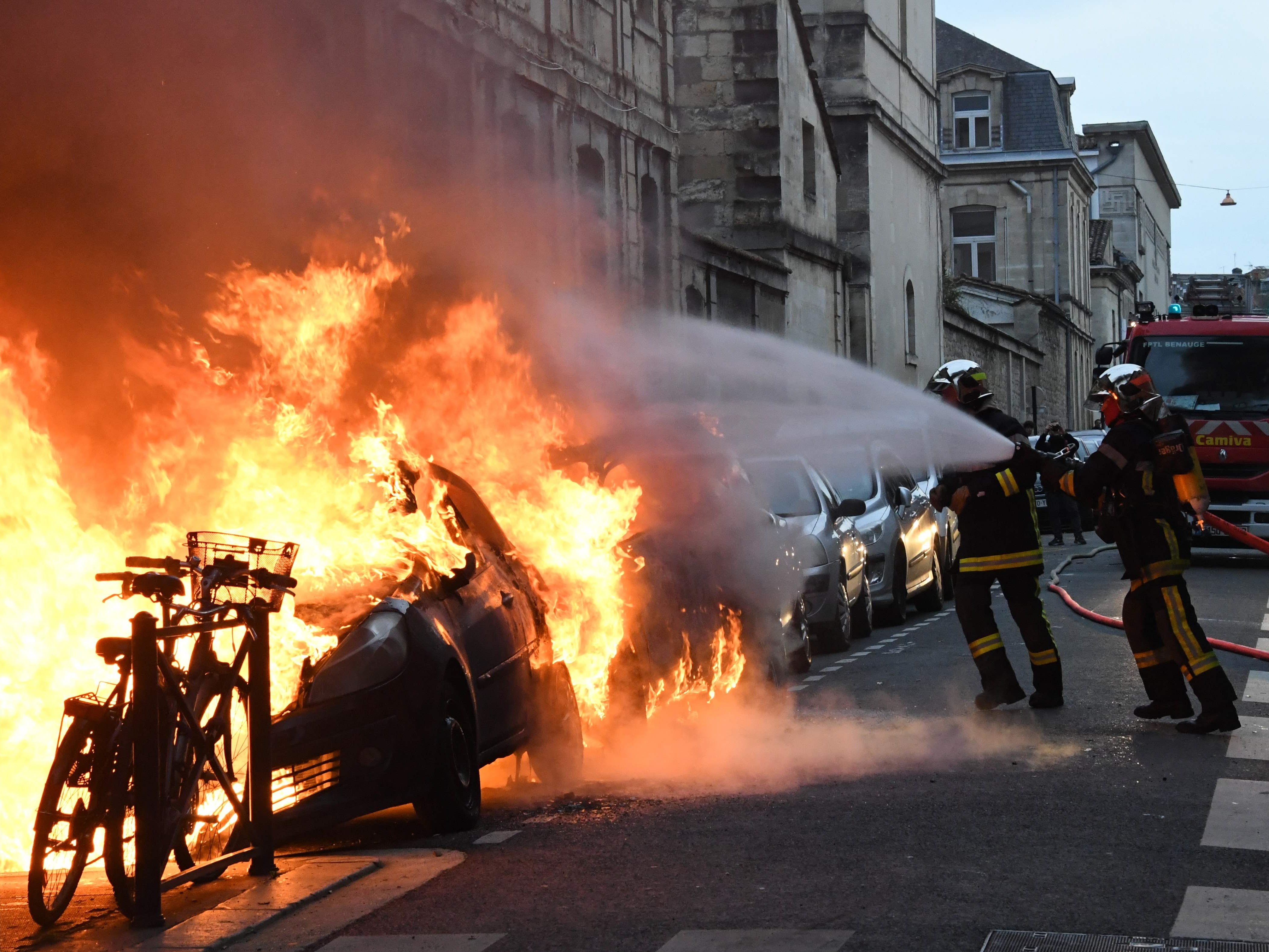 Firemen are at work to extinguish a fire on the sideline of a yellow vests (Gilets jaunes) rally, on Feb. 9, 2019 in Bordeaux, during the 13th consecutive Saturday of demonstrations.