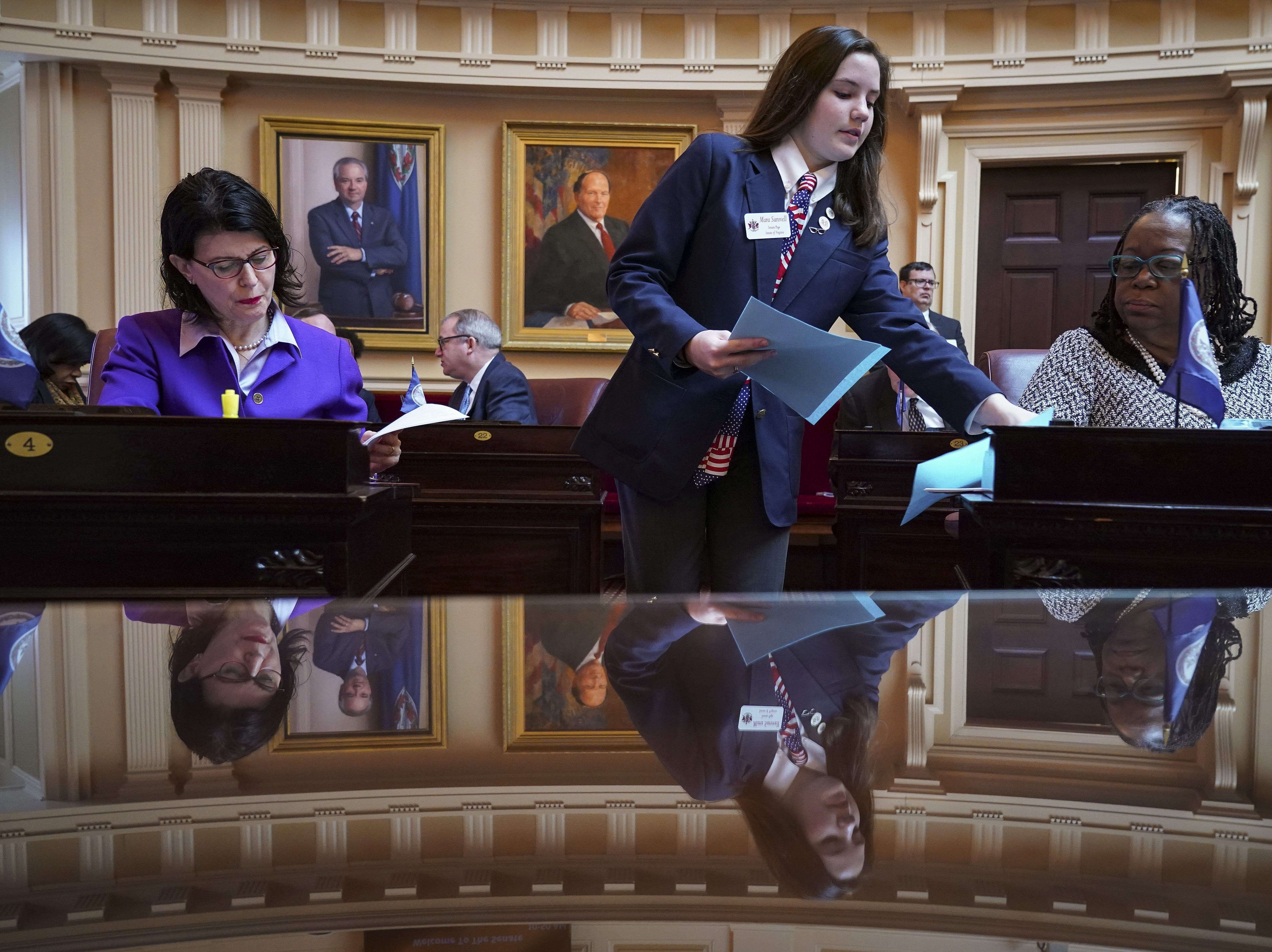 A Senate page hands out documents to lawmakers, including State Senator Mamie Locke, right, during a Senate session at the Virginia State Capitol, February 8, 2019 in Richmond, Va.