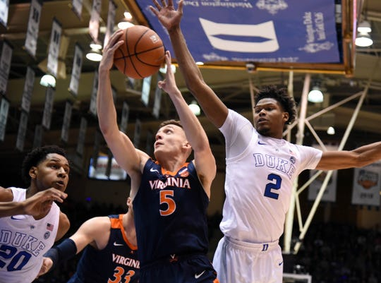 Virginia Cavaliers guard Kyle Guy (5) lays the ball up in front of Duke Blue Devils forward Cam Reddish (2) during the first half at Cameron Indoor Stadium.