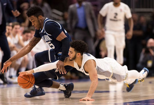 Villanova Wildcats forward Saddiq Bey (15) and Marquette Golden Eagles guard Markus Howard (0) reach for a loose ball during the second half at Fiserv Forum.