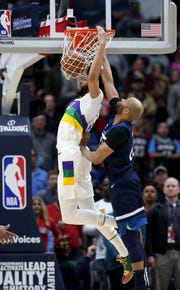 New Orleans Pelicans forward Anthony Davis dunks while defended by Minnesota Timberwolves forward Taj Gibson in the first quarter.