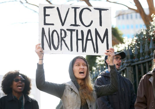 Geraldine Mabagos, of Richmond, holds a sign during a protest in Richmond calling for Governor Ralph Northam to resign on Monday Feb. 4, 2019. Northam has rebuffed widespread calls for his resignation after a racist photo surfaced Friday in his 1984 medical school yearbook page.