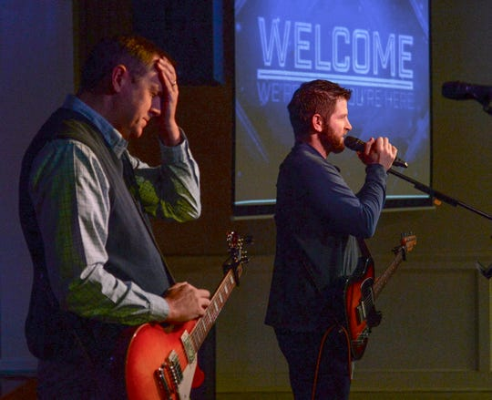 Stephen Jones, left, and Adam Comstock, contemporary worship leader, join in a worship song during the 11 a.m. service at Trinity United Methodist Church in Anderson Sunday. At the same time, a traditional service is held in the main sanctuary.