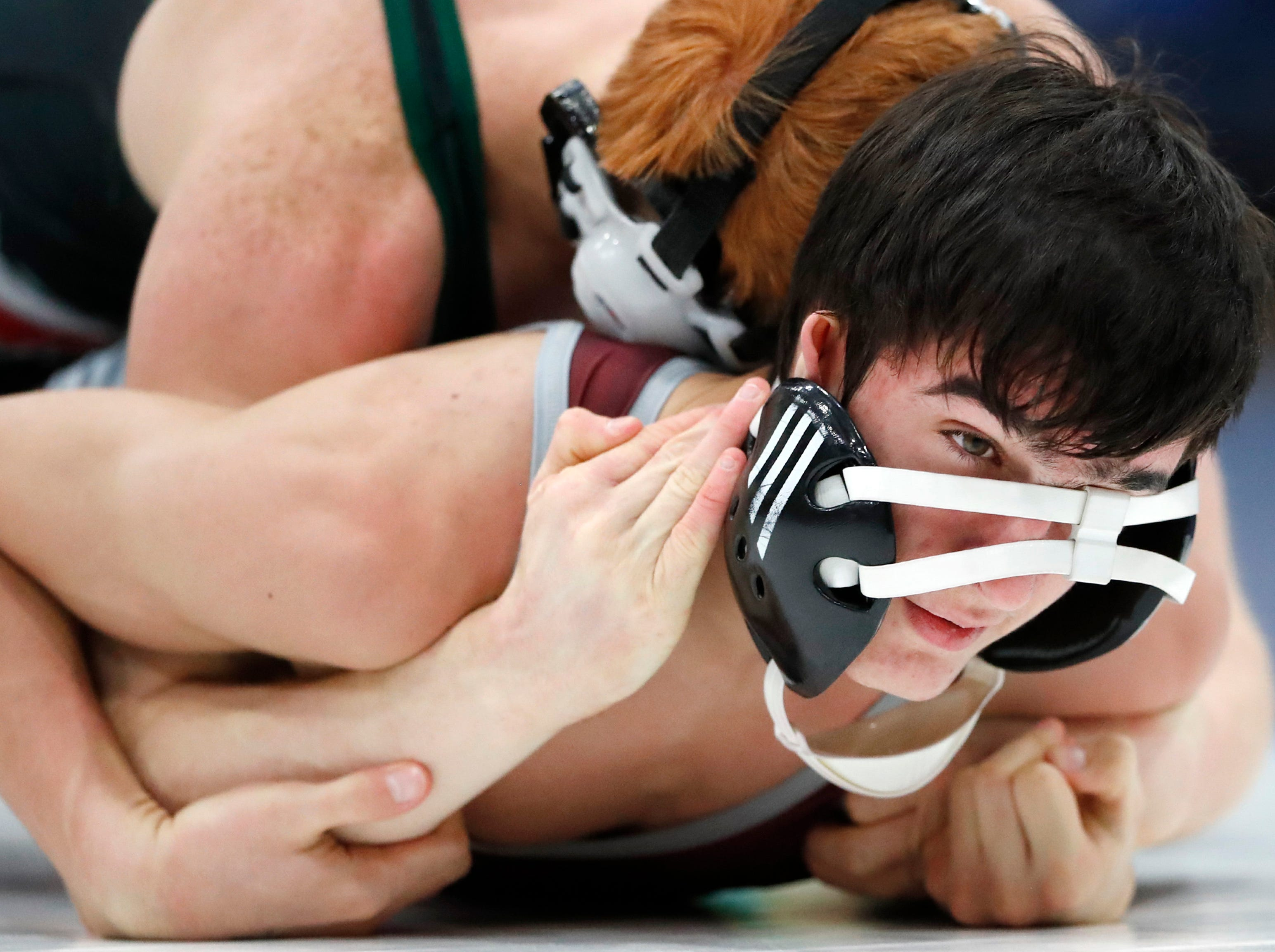 Berlin's Scott McGibbon holds down Winneconne's Sonny Barone as his headgear slides down his face during their 132-pound match in the D2 wrestling regional Saturday Feb. 9, 2019, in Little Chute, Wis.