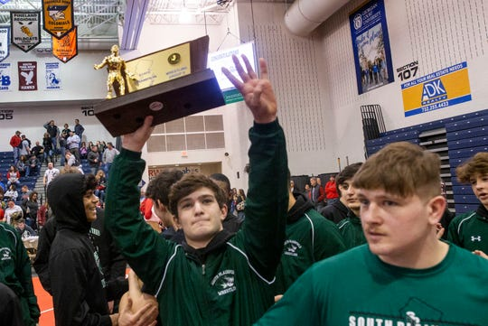 South Plainfield's Joe Sacco holds up his team's trophy and signals that its their four straight. South Plainfield defeats  High Point 46-26 in Group II Wrestling Team Championship.