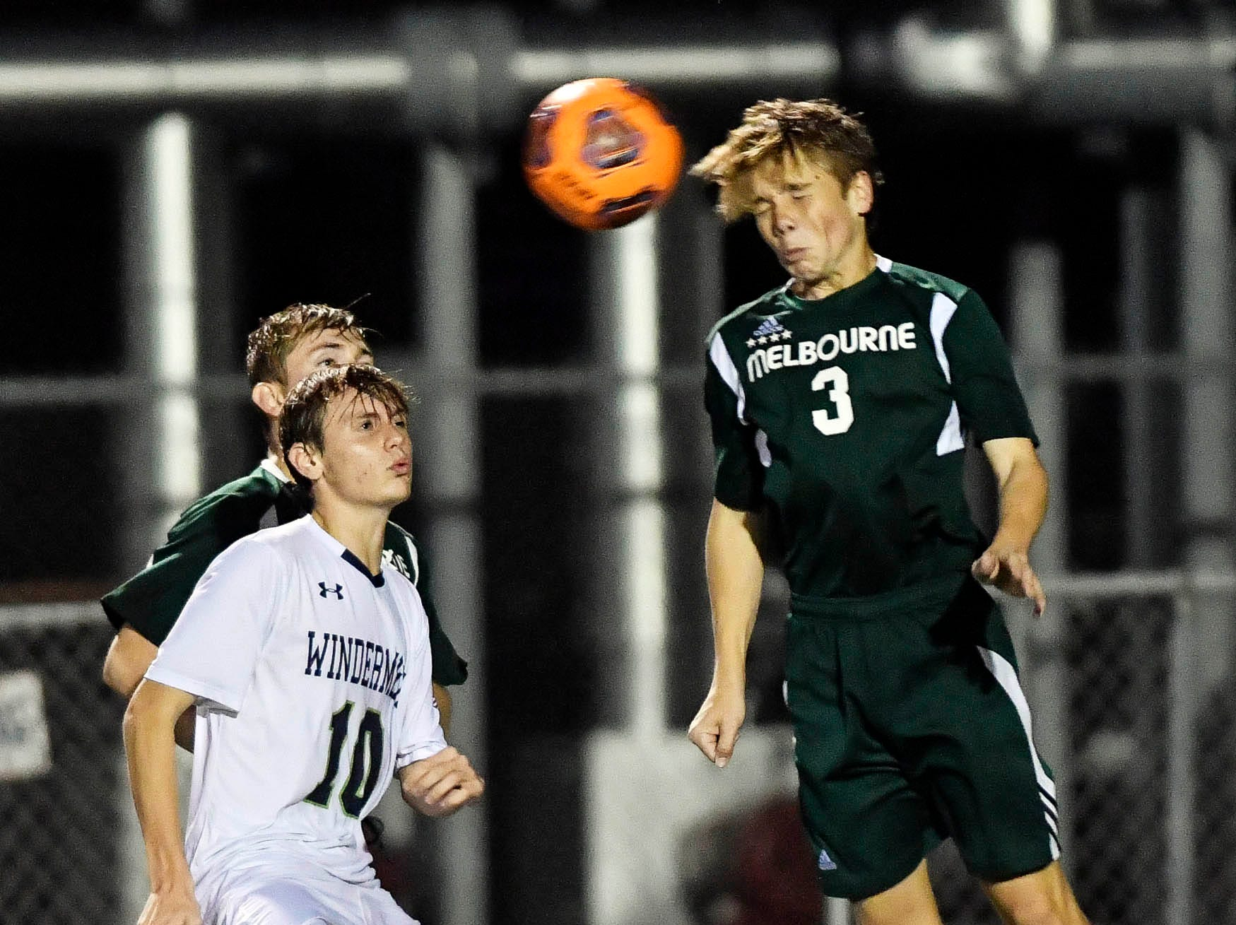 Luke Russo of Melbourne heads the ball away from a Windermere player during Saturday's Class 4A boys soccer regional semifinal.