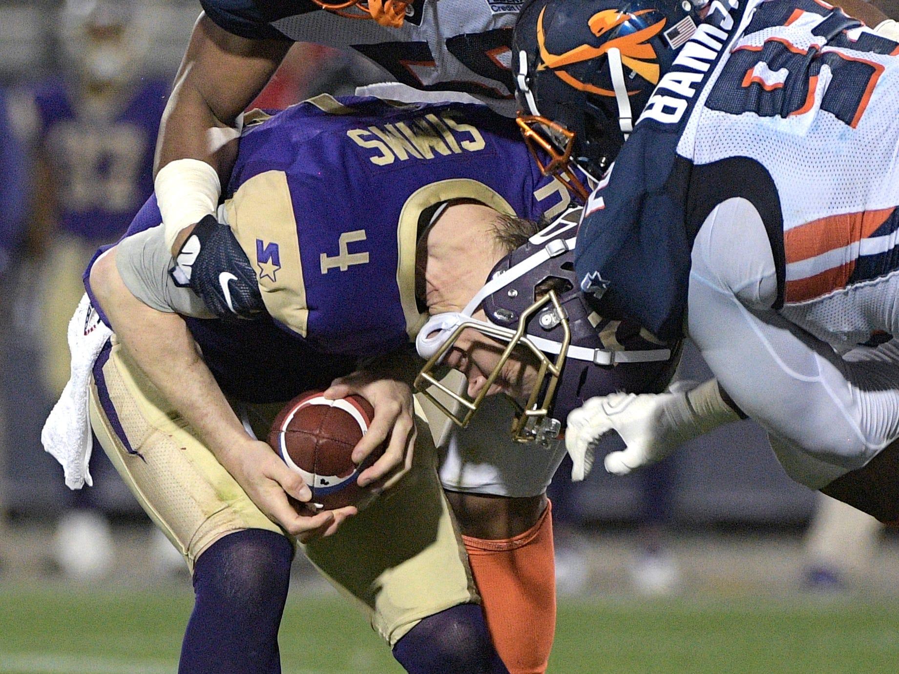 Atlanta Legends quarterback Matt Simms (4) is sacked by Orlando Apollos linebacker Christian French (58) and Josh Banks Sr. (92) during the first half of an Alliance of American Football game Saturday, Feb. 9, 2019, in Orlando, Fla. (AP Photo/Phelan M. Ebenhack)
