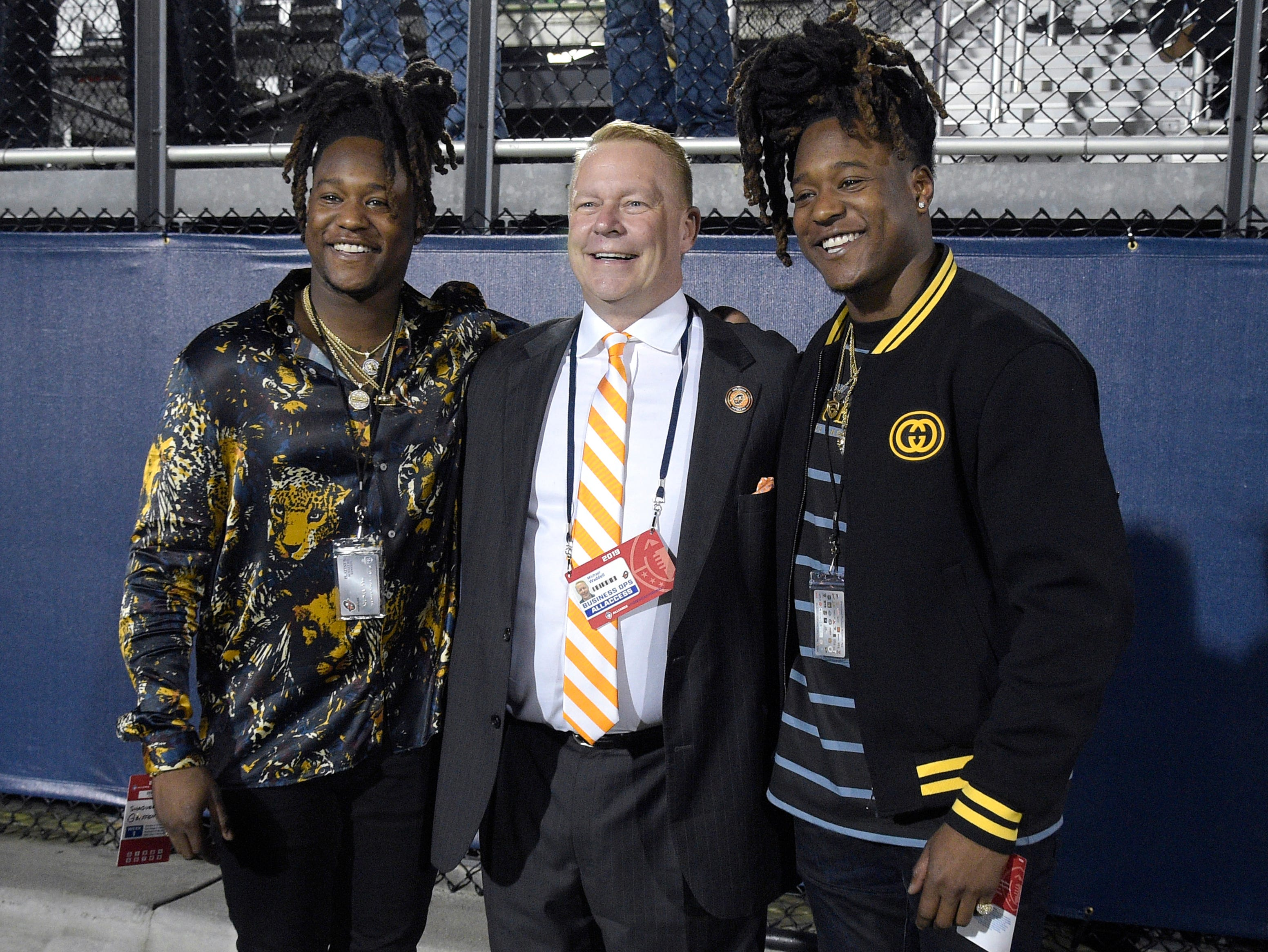 Orlando Apollos president Michael Waddell, center, poses on the sideline with Seattle Seahawks linebacker Shaquem Griffin, left, and defensive back Shaquill Griffin during the first half of the team's Alliance of American Football game against the Atlanta Legends on Saturday, Feb. 9, 2019, in Orlando, Fla. (AP Photo/Phelan M. Ebenhack)