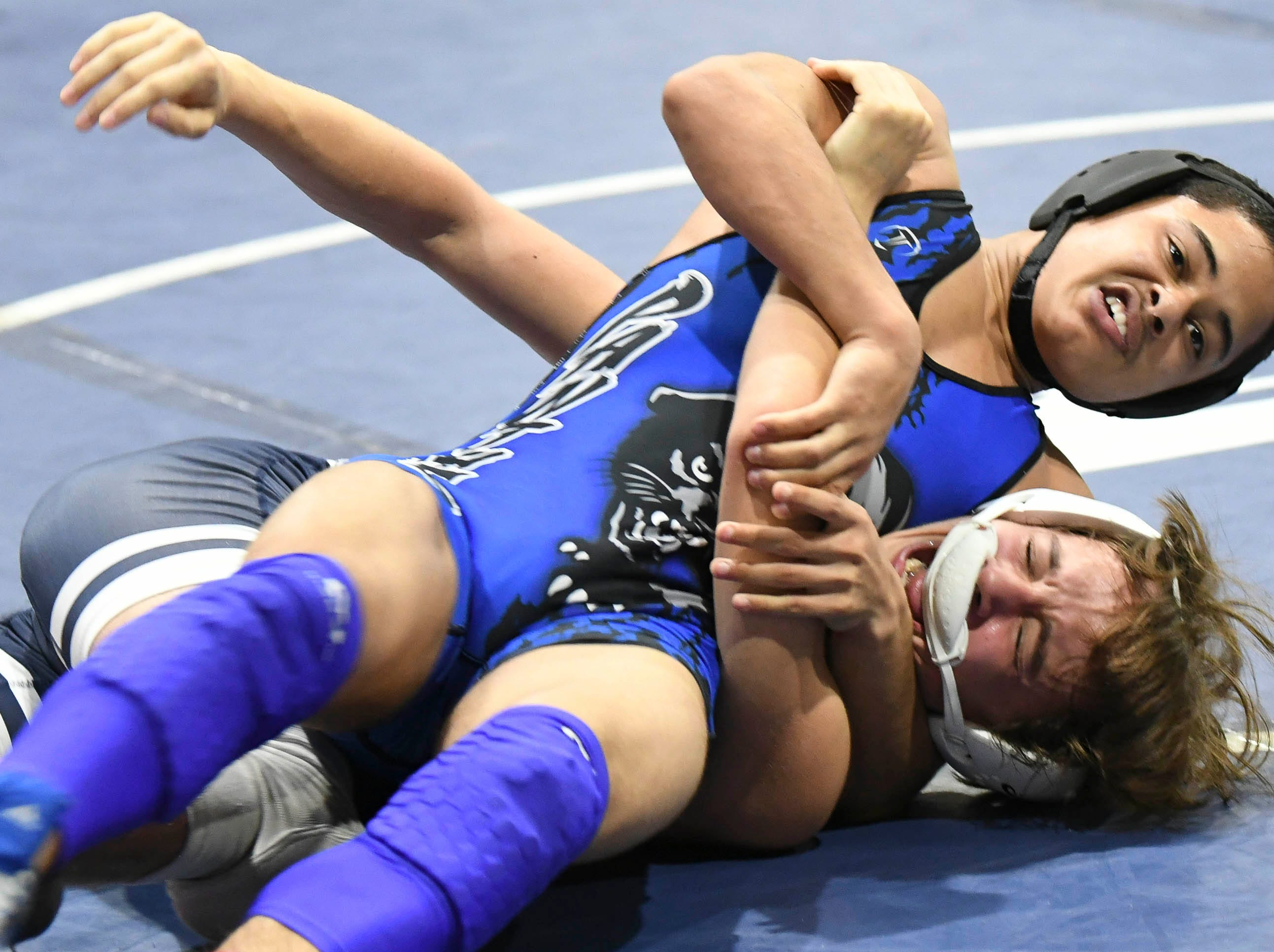 Prynce Rivera of Heritage wrestles Caleb Lovin of Cocoa Beach Saturday during the Cape Coast Conference Wrestling Meet.