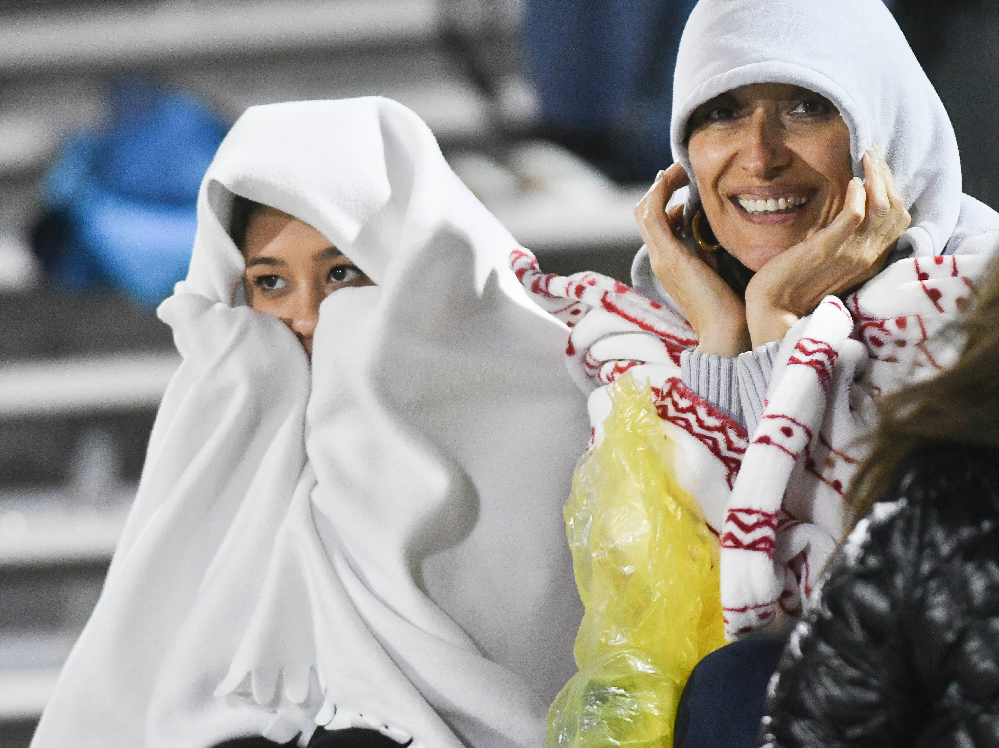 Soccer fans bundle up against the cold and wet weather during Saturday's Class 4A boys soccer regional semifinal between Melbourne and Windermere.