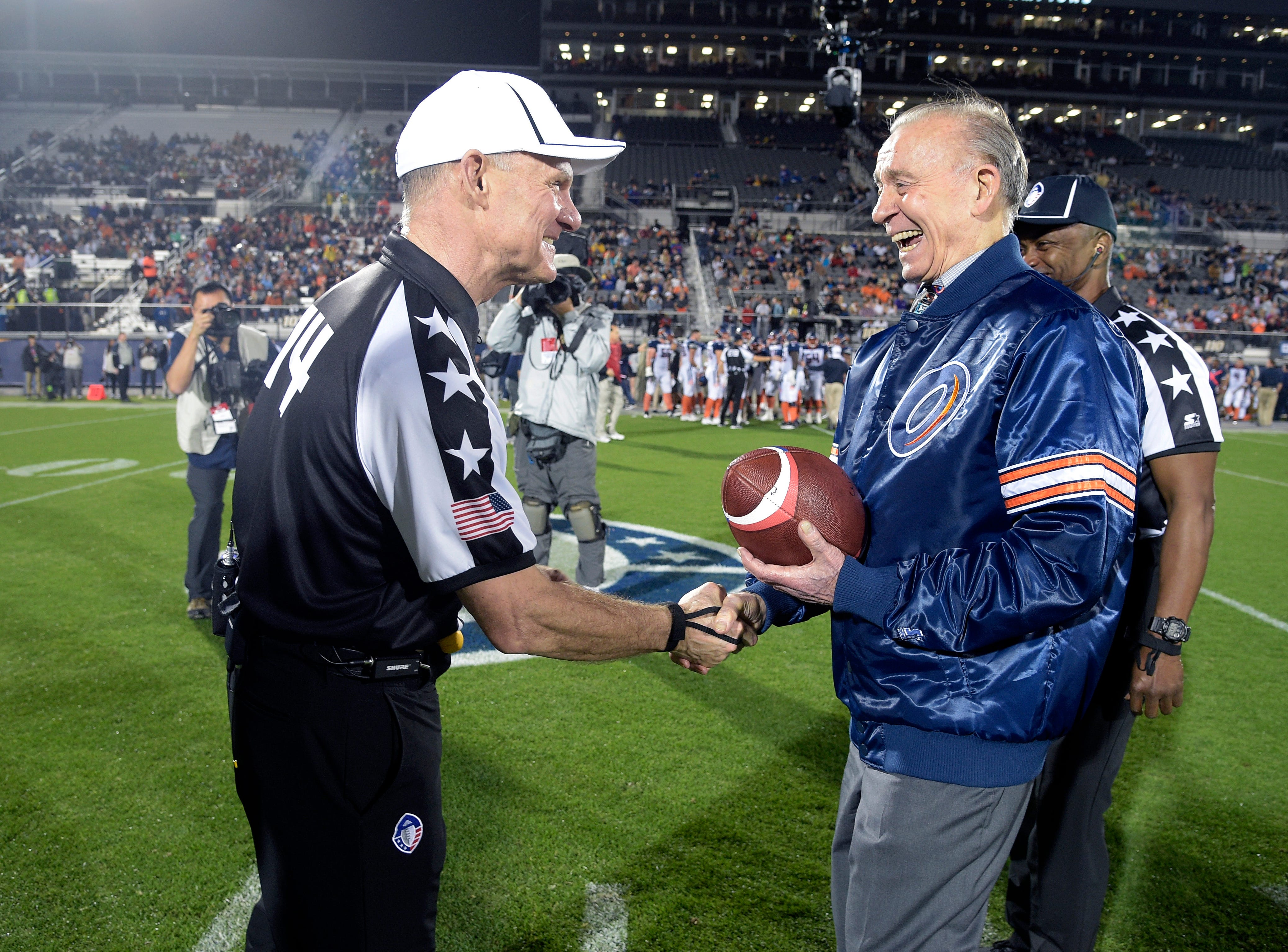 Apollo VII astronaut Walter Cunningham, right, delivers the game ball to official John O'Neill on the field before an Alliance of American Football game between the Orlando Apollos and the Atlanta Legends on Saturday, Feb. 9, 2019, in Orlando, Fla. (AP Photo/Phelan M. Ebenhack)