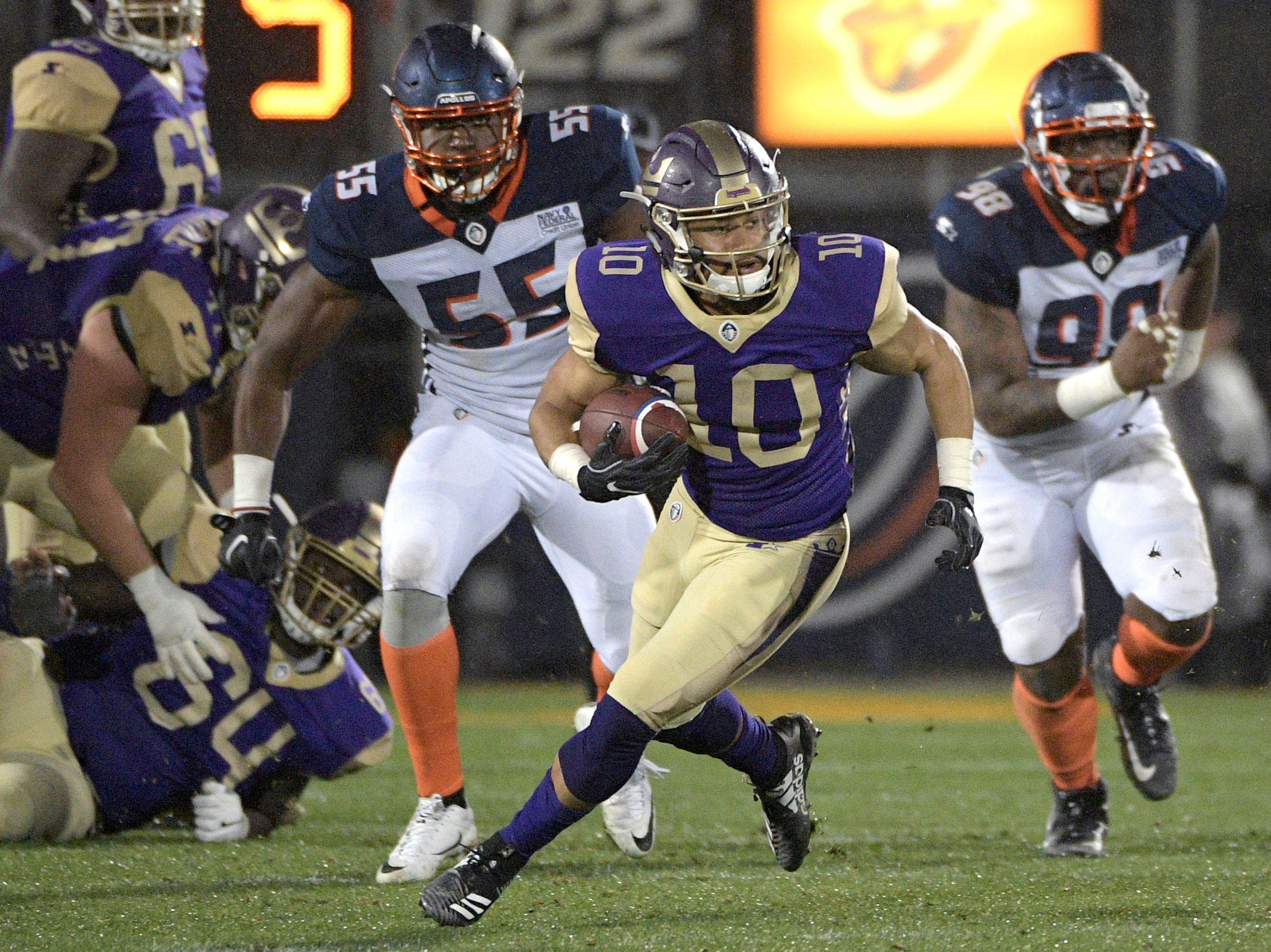 Atlanta Legends receiver Justin Thomas (10) runs with a recption in front of Orlando Apollos linebacker Andrew Ankrah (55) and defensive end Anthony Moten Jr. (98) during the second half of an Alliance of American Football game Saturday, Feb. 9, 2019, in Orlando, Fla. (AP Photo/Phelan M. Ebenhack)