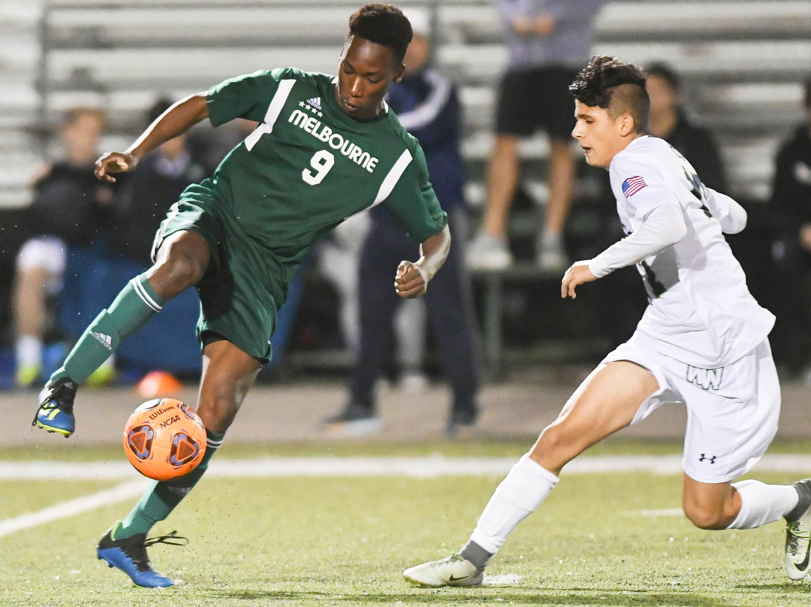 Melbourne's Osas Osaro maneuvers the ball around a Windermere defender during Saturday's Class 4A boys soccer regional semifinal.