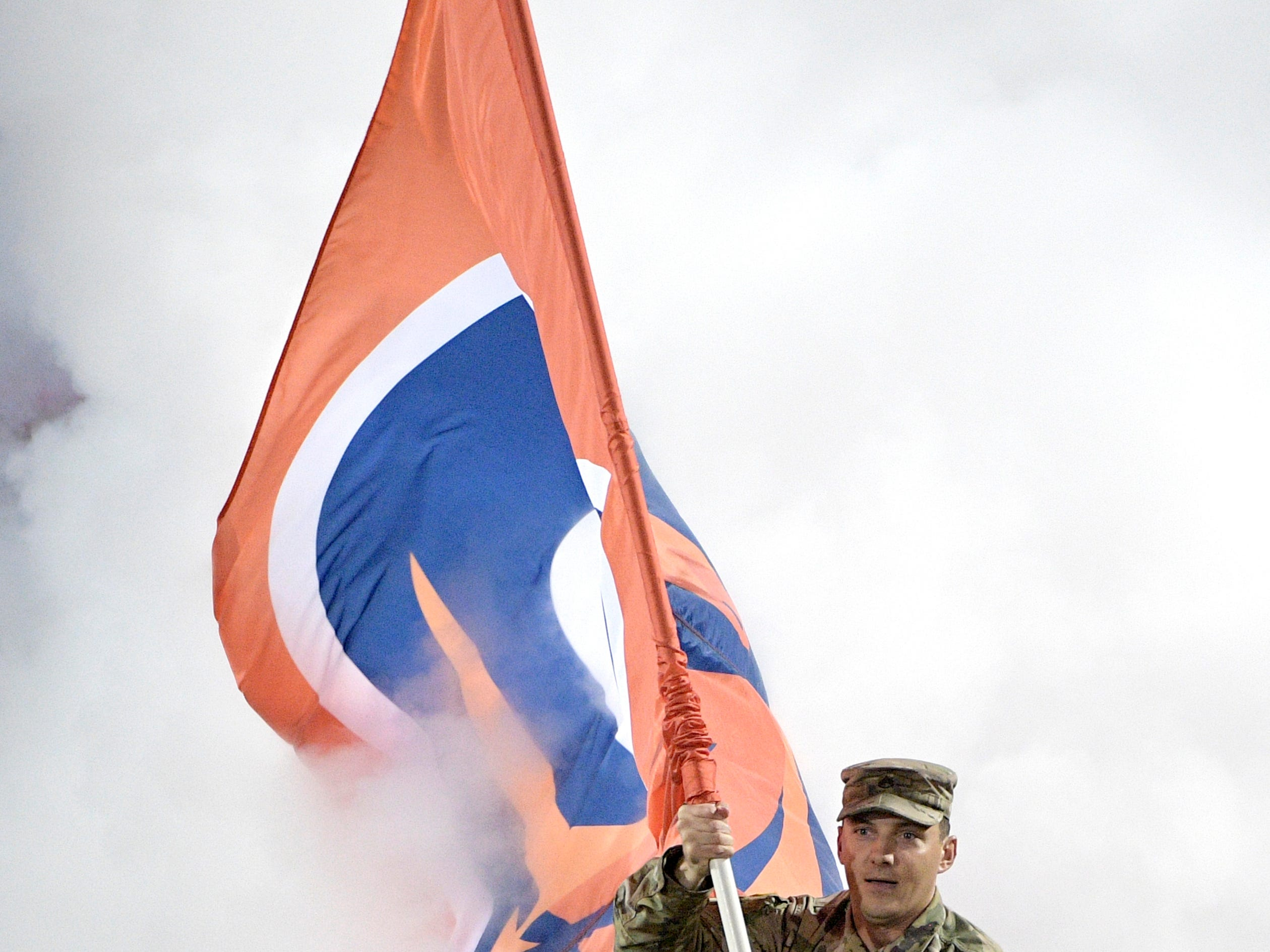 A member of the U.S. military carries a team flag onto the field before an Alliance of American Football game between the Orlando Apollos and the Atlanta Legends on Saturday, Feb. 9, 2019, in Orlando, Fla. (AP Photo/Phelan M. Ebenhack)
