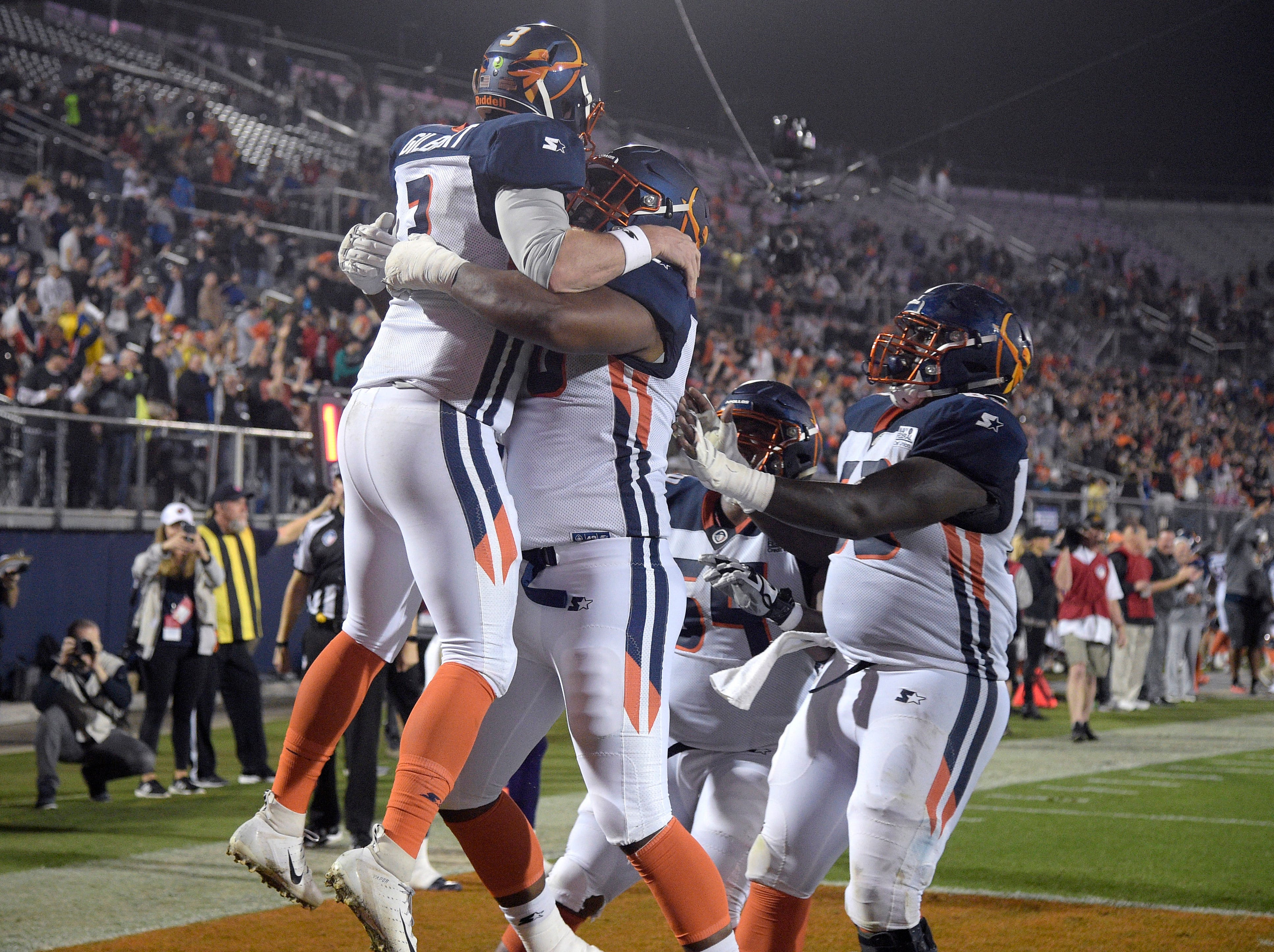 Orlando Apollos quarterback Garrett Gilbert, left, is congratulated by teammates after catching a pass from receiver Jalin Marshall for a 5-yard touchdown during the first half of an Alliance of American Ffootball game against the Atlanta Legends on Saturday, Feb. 9, 2019, in Orlando, Fla. (AP Photo/Phelan M. Ebenhack)