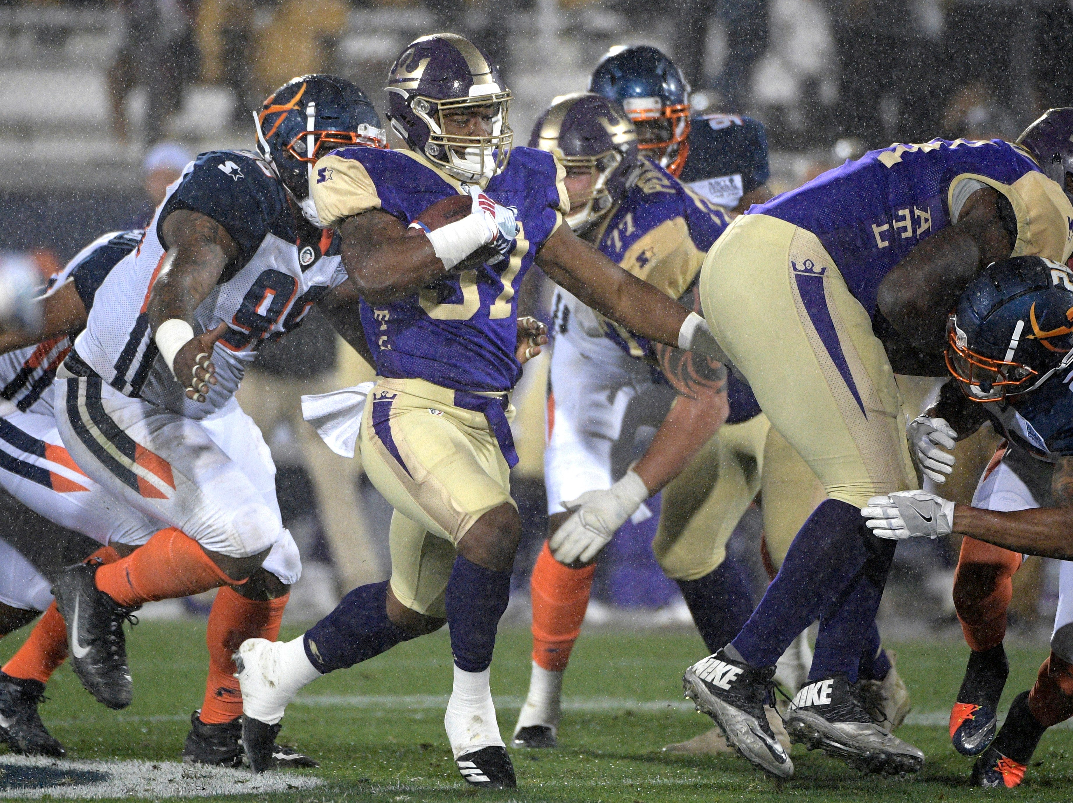 Atlanta Legends running back Lawrence Pittman rushes in front of Orlando Apollos defensive end Anthony Moten Jr. (98) during the second half of an Alliance of American Football game Saturday, Feb. 9, 2019, in Orlando, Fla. (AP Photo/Phelan M. Ebenhack)