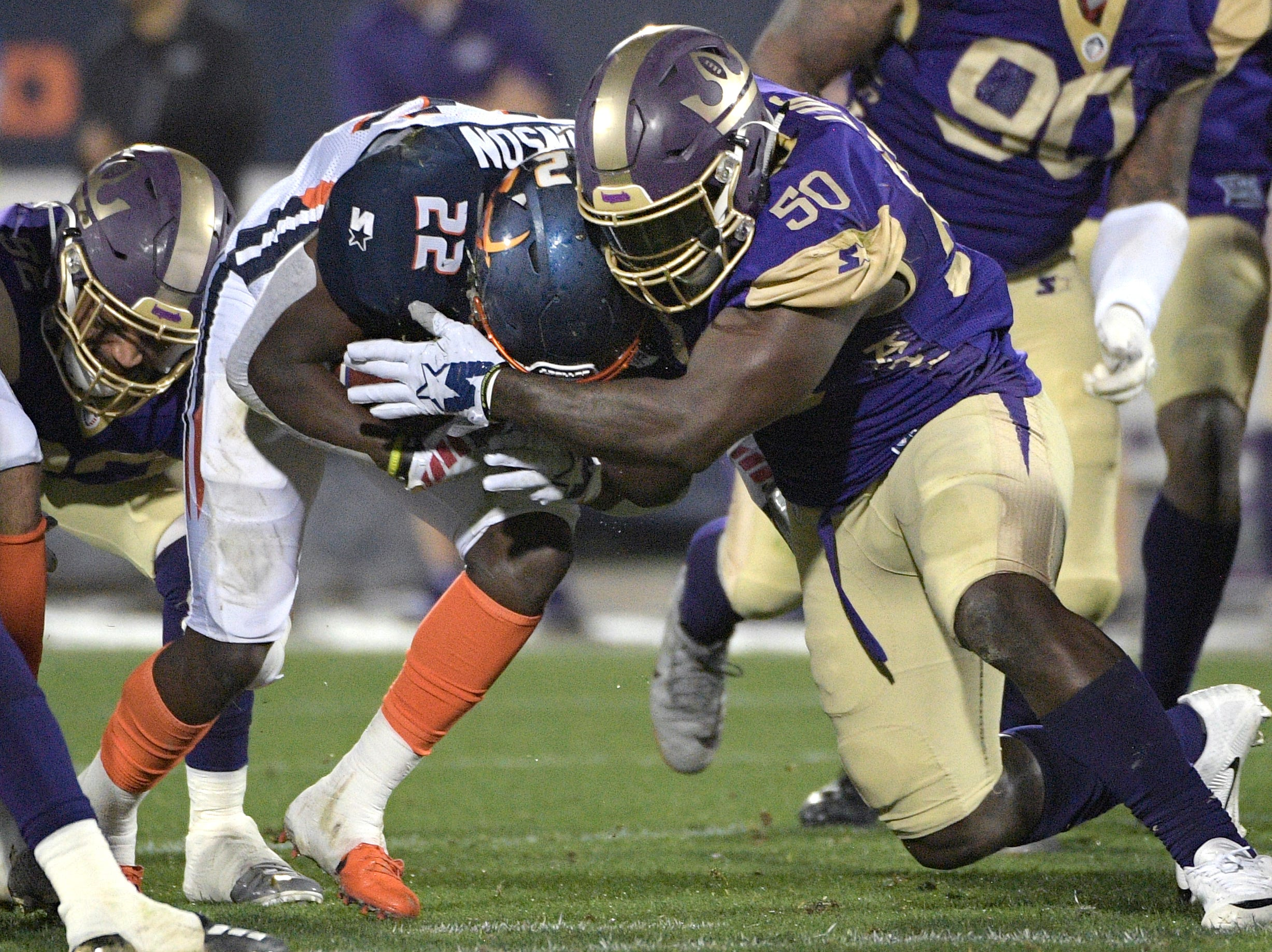 Orlando Apollos running back D'Ernest Johnson (22) is stopped by Atlanta Legends linebacker Jeff Luc (50) after rushing for a short gain during the first half of an Alliance of American Football game Saturday, Feb. 9, 2019, in Orlando, Fla. (AP Photo/Phelan M. Ebenhack)