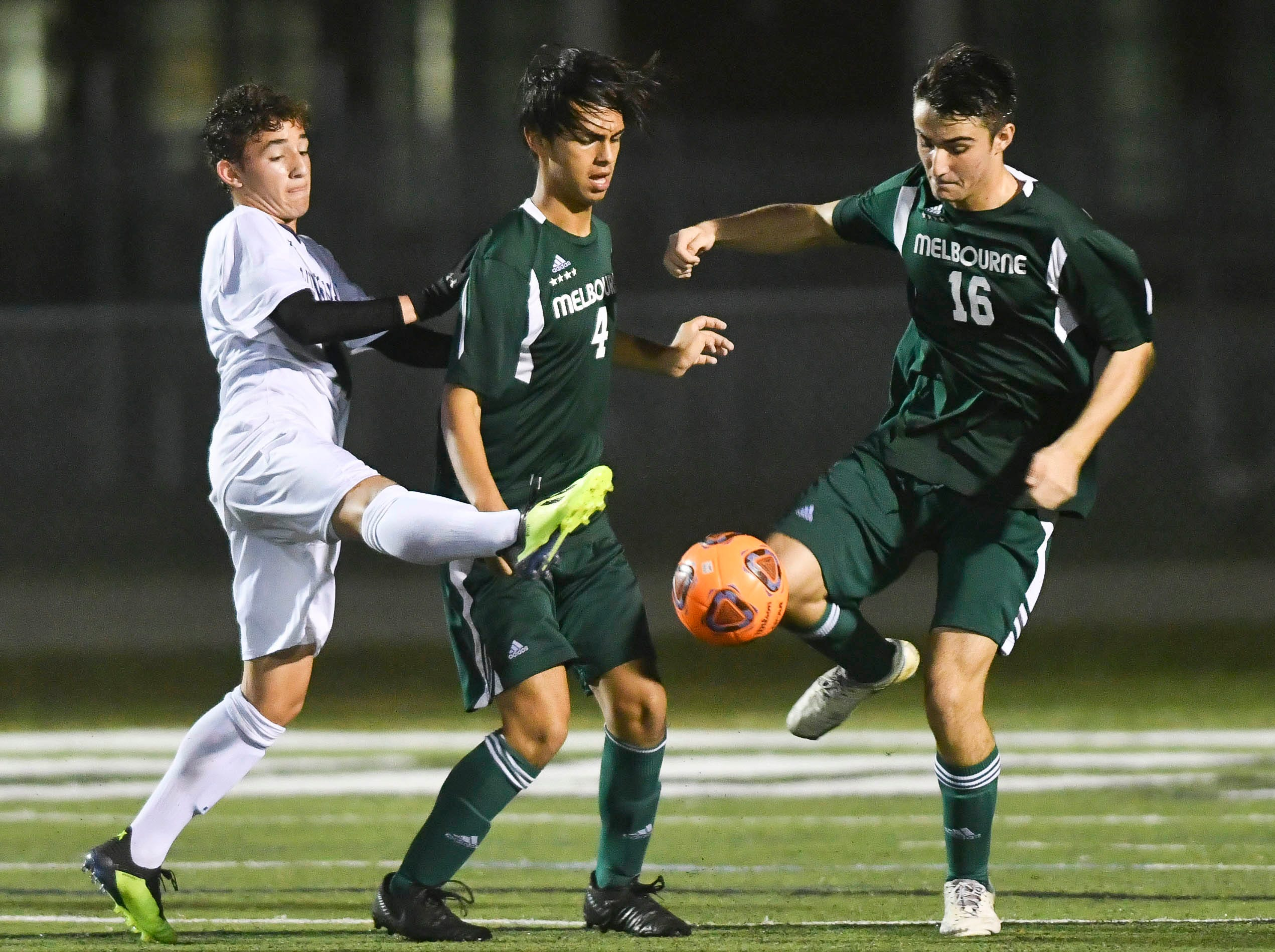 Nick Martinez (4) and Calvin MacDonald of Melbourne direct the ball away from a Windermere attacker during Saturday's Class 4A boys soccer regional semifinal.