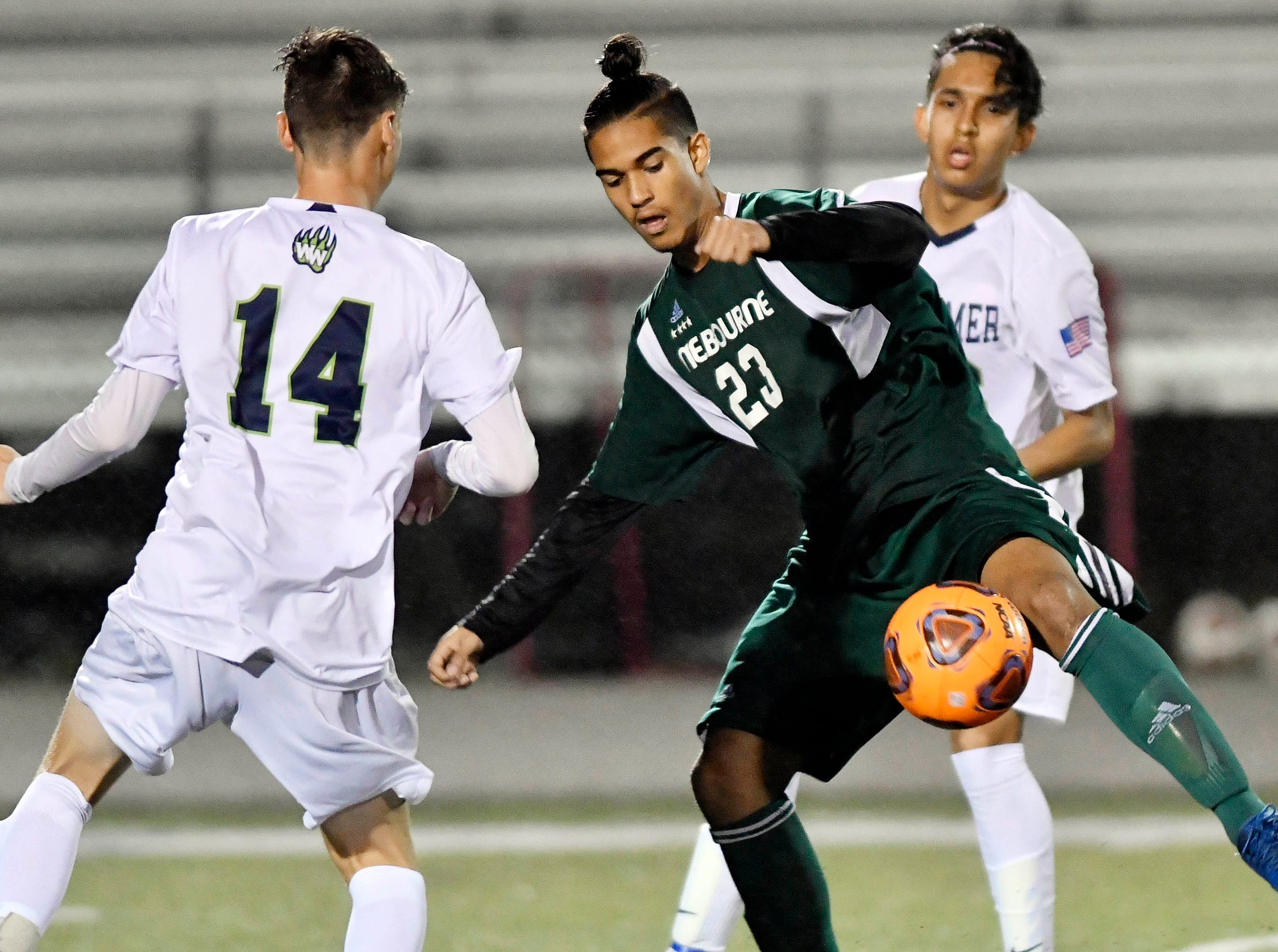 Melbourne's Mekhi Robinson maneuvers between a pair of Windermere defenders during Saturday's Class 4A boys soccer regional semifinal.