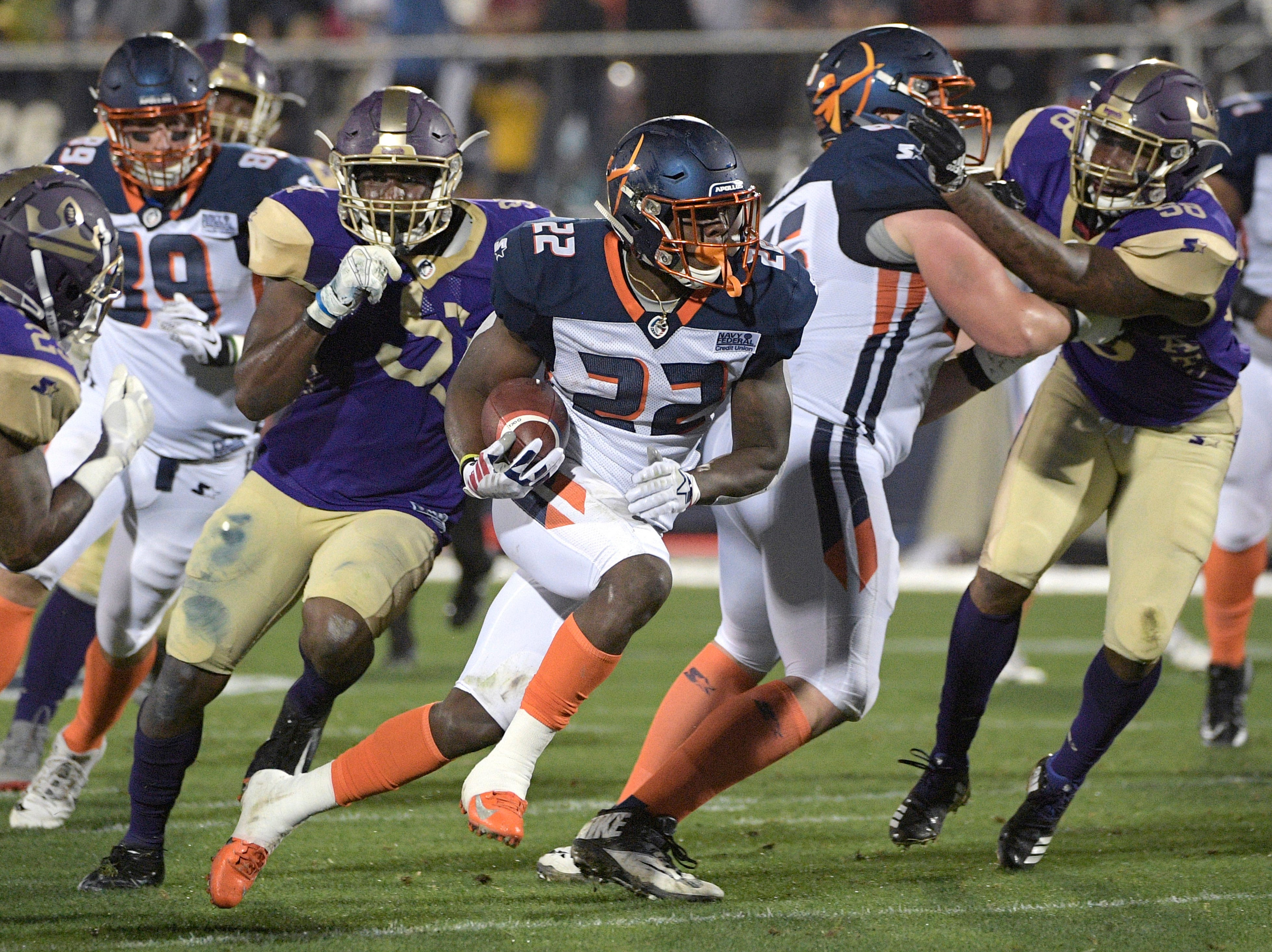 Orlando Apollos running back D'Ernest Johnson (22) rushes for yardage in front of Atlanta Legends defensive back Desmond Lawrence, left, defensive lineman J.T. Jones, center, and linebacker Brandon Watts (58) during the first half of an Alliance of American Football game Saturday, Feb. 9, 2019, in Orlando, Fla. (AP Photo/Phelan M. Ebenhack)