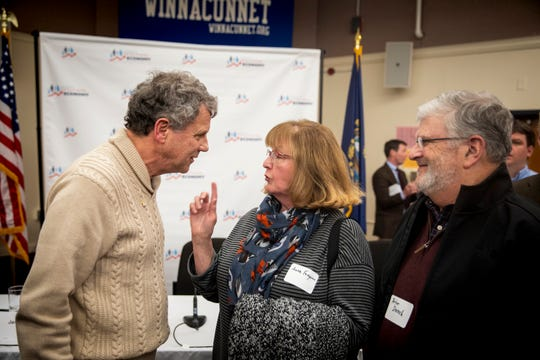 """Senator Sherrod Brown meets Anne Ferguson and Peter Drench after a roundtable with the Campaign for a Family Friendly Economy in a lecture hall at Winnacunnet High School in Hampton, N.H. Friday, February 8, 2019. Ferguson wore her Cleveland pin to the roundtable and talked to Brown about her Ohio roots. The roundtable was part of Brown's """"Dignity of Work"""" and his first stop in New Hampshire. Brown traveled to Iowa last week and will visit Nevada and South Carolina in the next few weeks."""