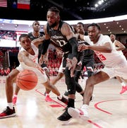 Cincinnati forward Eliel Nsoseme, center, chases a loose ball between Houston guard Armoni Brooks, left, and guard Dejon Jarreau, right, during the first half of an NCAA college basketball game Sunday, Feb. 10, 2019, in Houston.