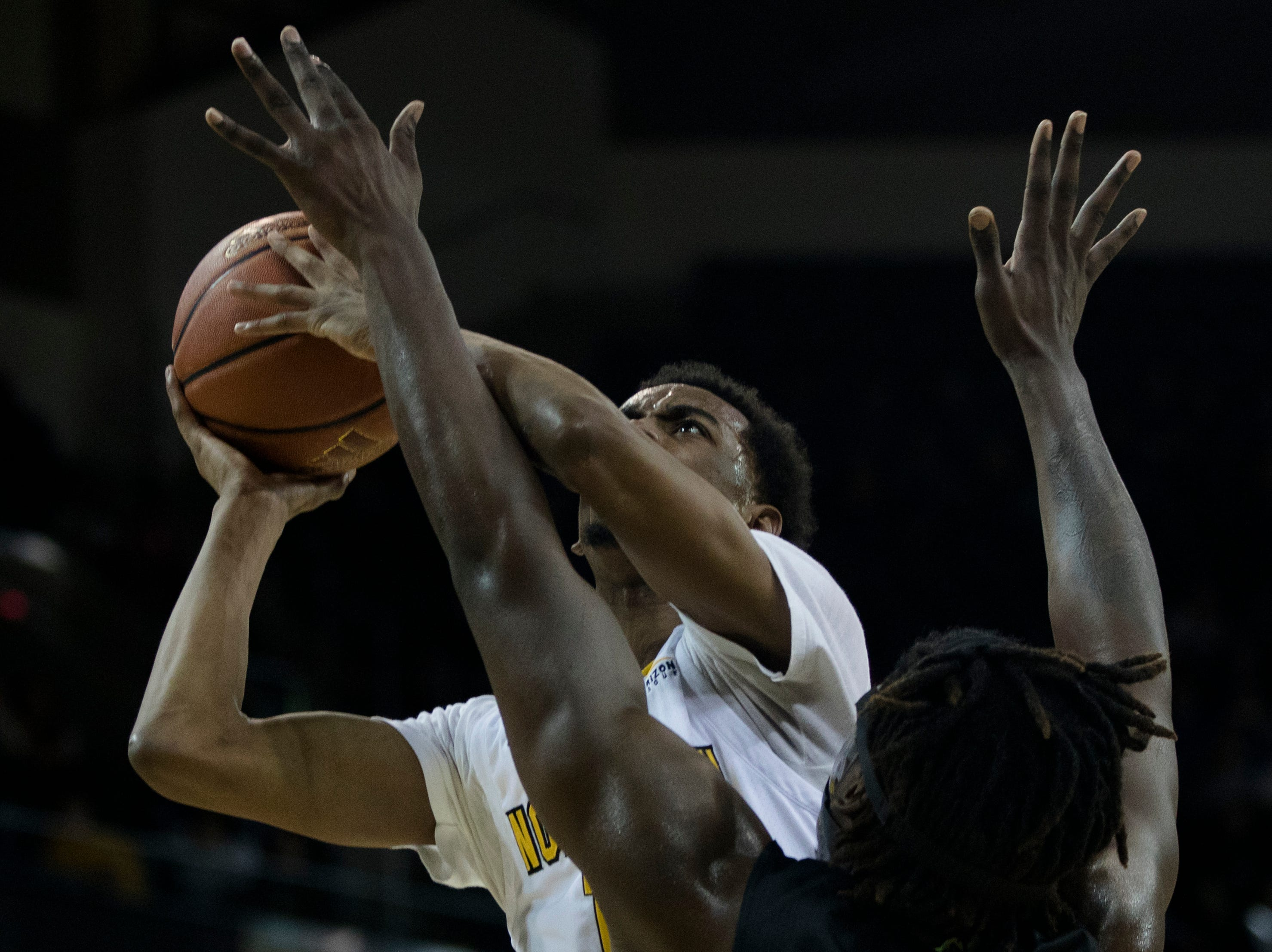 Northern Kentucky Norse guard Jalen Tate (11) lays the ball up around Oakland Golden Grizzlies forward Xavier Hill-Mais (14) in the first half of the men's NCAA basketball game between Northern Kentucky Norse and Oakland Golden Grizzlies on Saturday, Feb. 9, 2019, at BB&T Arena in Highland Heights, Ky.