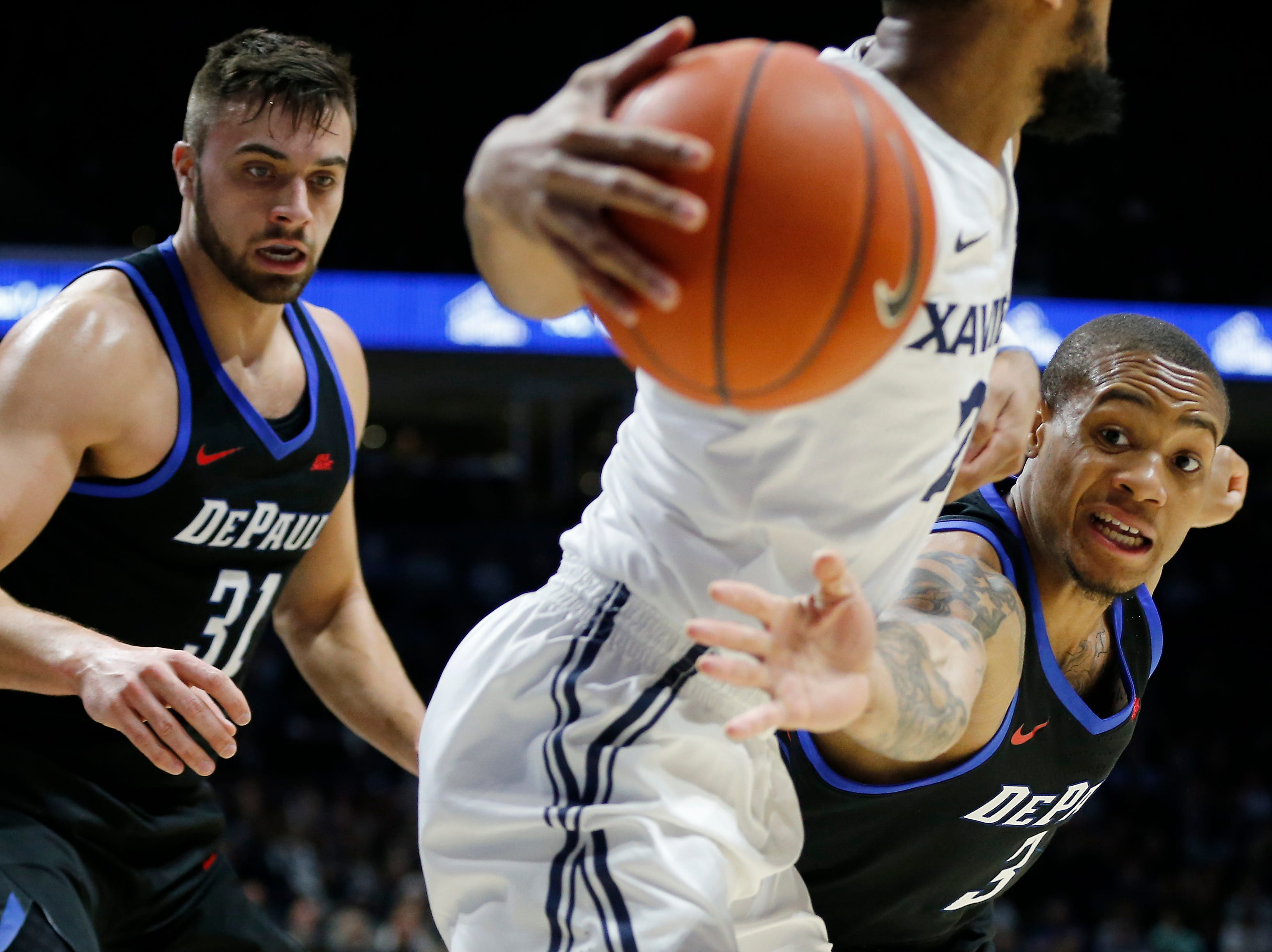 DePaul Blue Demons guard Devin Gage (3) reaches in on Xavier Musketeers guard Kyle Castlin (2) in the first half of the NCAA Big East Conference game between the Xavier Musketeers and the DePaul Blue Demons at the Cintas Center in Cincinnati on Saturday, Feb. 9, 2019.