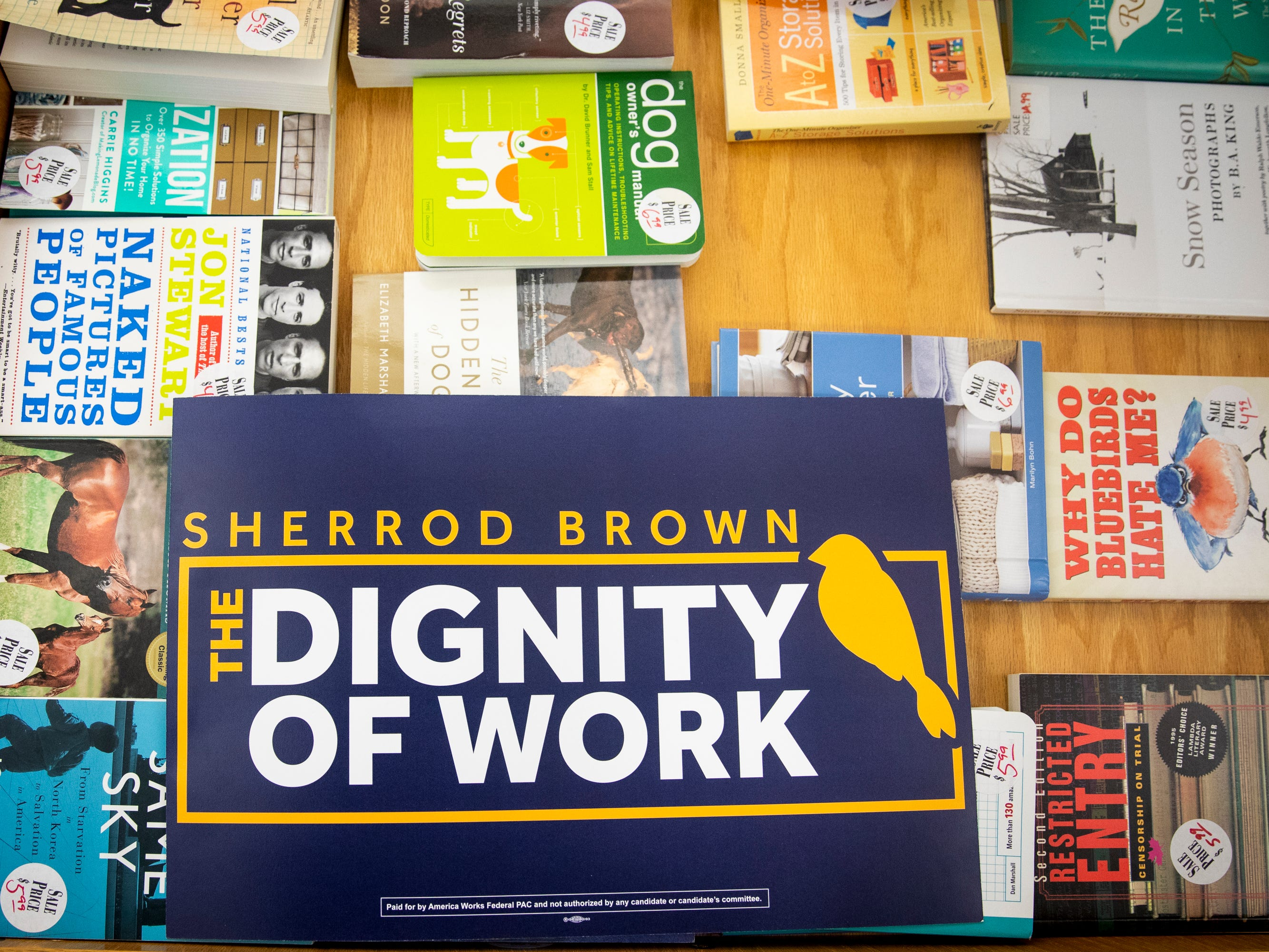 "A ""Dignity of Work"" tour sign lays on top of the bargain books at Gibson's Bookstore in Concord, N.H. where Senator Sherrod Brown does a meet and greet Saturday, February 9, 2019."