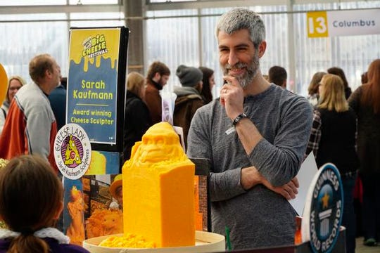 Jimmy Bonamino of Jungle Jim's smiles as Sarah Kaufman shows a young girl the start of a cheese sculpture at the 2019 Big Cheese Festival, at Jungle Jim's International Market.