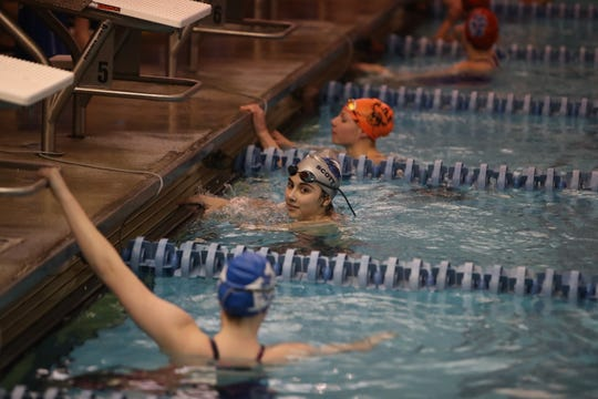 Caroline Meister [center] from Scott High School wins the Girls 50 Yard Freestyle at the Regional Final at the KHSAA Regional Swimming Finals in Erlanger, Kentucky.