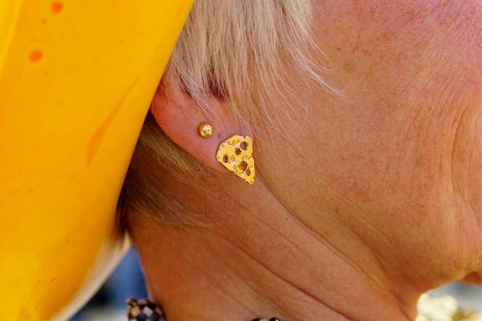 Sarah Kaufman, a Wisconsin native, former Jungle Jim's employee, and current cheese sculptress sports themed earrings as she carves a block of cheddar a the annual Big Cheese Festival, at Jungle Jim's International Market, Saturday, Feb. 9, 2019.