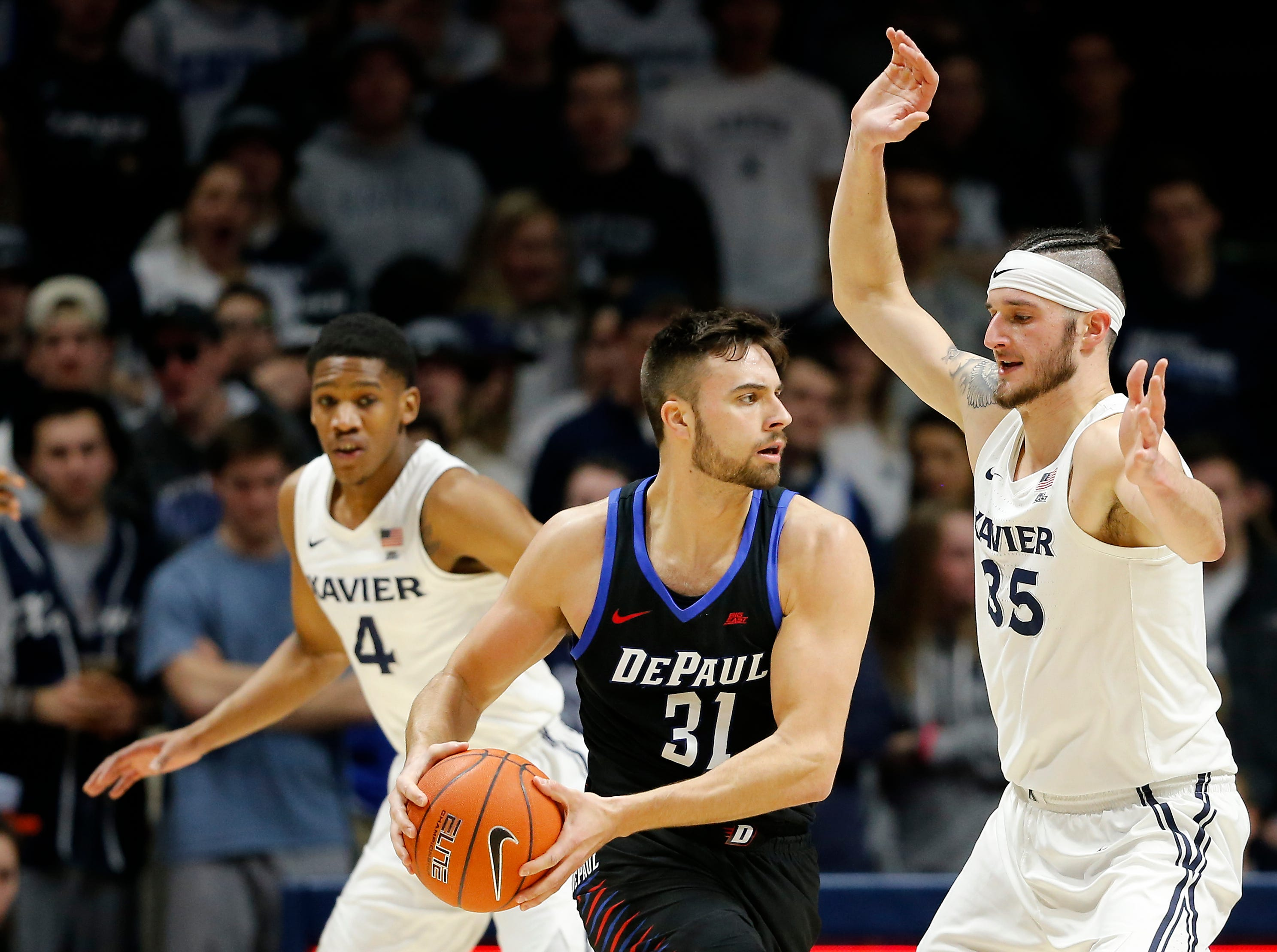 DePaul Blue Demons guard Max Strus (31) passes around Xavier Musketeers forward Zach Hankins (35) in the second half of the NCAA Big East Conference game between the Xavier Musketeers and the DePaul Blue Demons at the Cintas Center in Cincinnati on Saturday, Feb. 9, 2019. Xavier lost its sixth game in a row, 74-62.