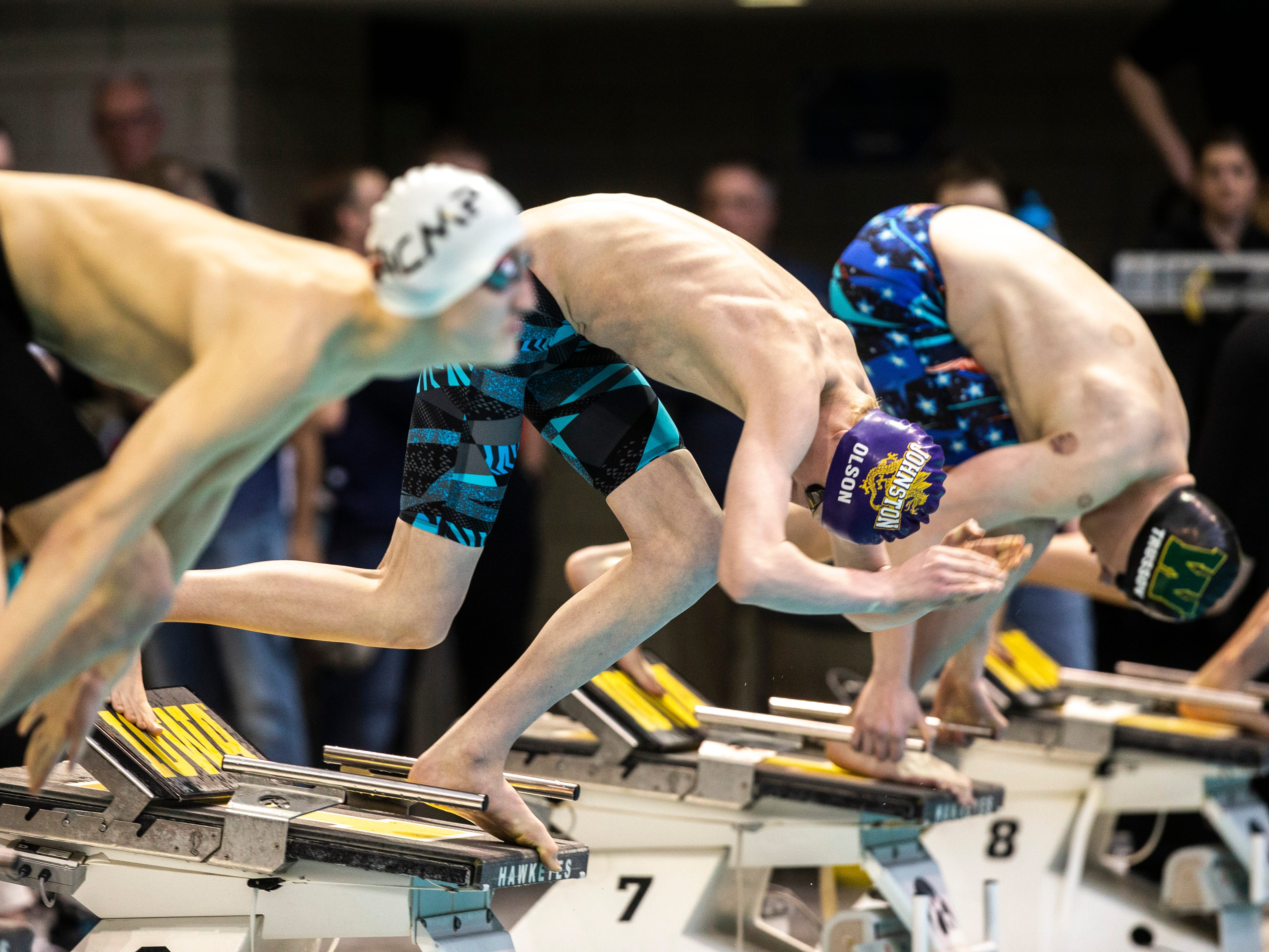 Johnston sophomore Spencer Olson leaps off the blocks in the first heat of 100 yard breaststroke during the Iowa boys' state swimming regional championship meet on Saturday, Feb. 9, 2019 at Campus Recreation and Wellness Center on the University of Iowa campus in Iowa City, Iowa. Olson finished 23rd overall, with a time of 1:03.02.