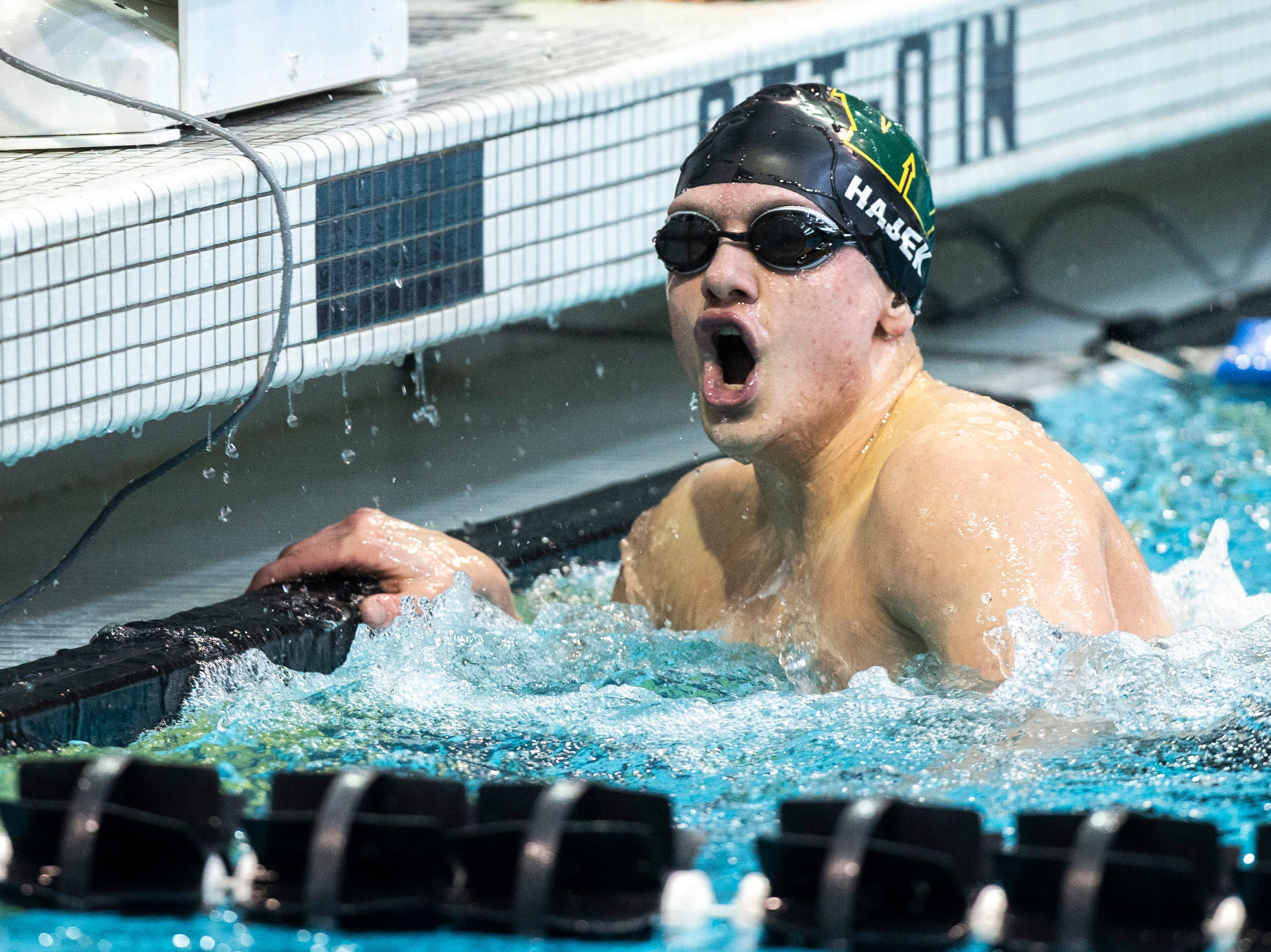 Iowa City West junior Izaak Hajek reacts after finishing first in the 100 yard butterfly during the Iowa boys' state swimming regional championship meet on Saturday, Feb. 9, 2019 at Campus Recreation and Wellness Center on the University of Iowa campus in Iowa City, Iowa. Hajek finished first overall, with a time of 49.45.