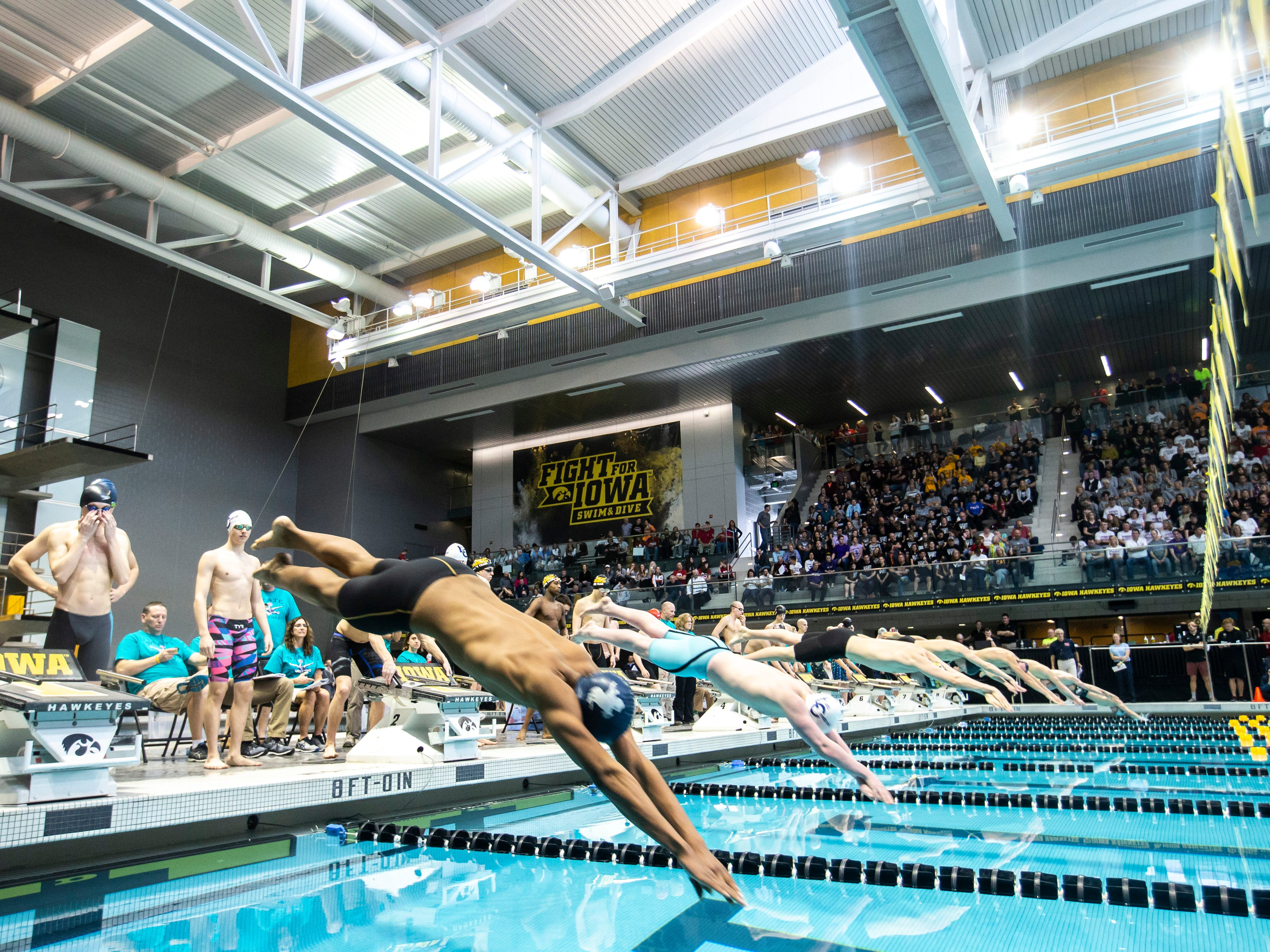 Competitors leap off the blocks in the 200 yard freestyle relay during the Iowa boys' state swimming regional championship meet on Saturday, Feb. 9, 2019 at Campus Recreation and Wellness Center on the University of Iowa campus in Iowa City, Iowa.