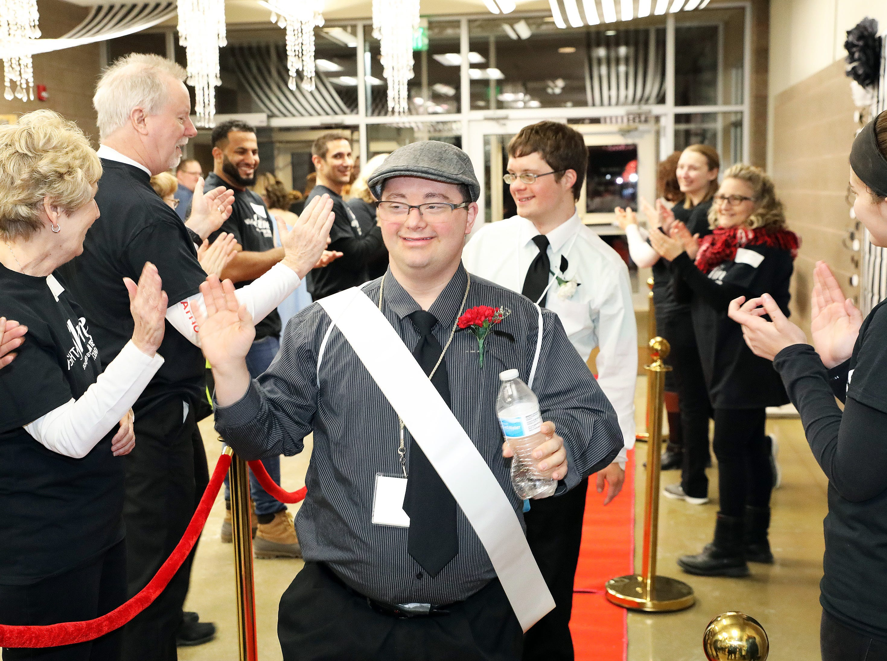 Jake Tyler is greeted with applause as he enters on the red carpet during the Night to Shine event at Prairie Ridge Church in Ankeny on Friday, Feb. 8, 2019. Sponsored by the Tim Tebow Foundation, the event for adults with special needs features a prom-like atmosphere with dancing, limo rides, food and more.