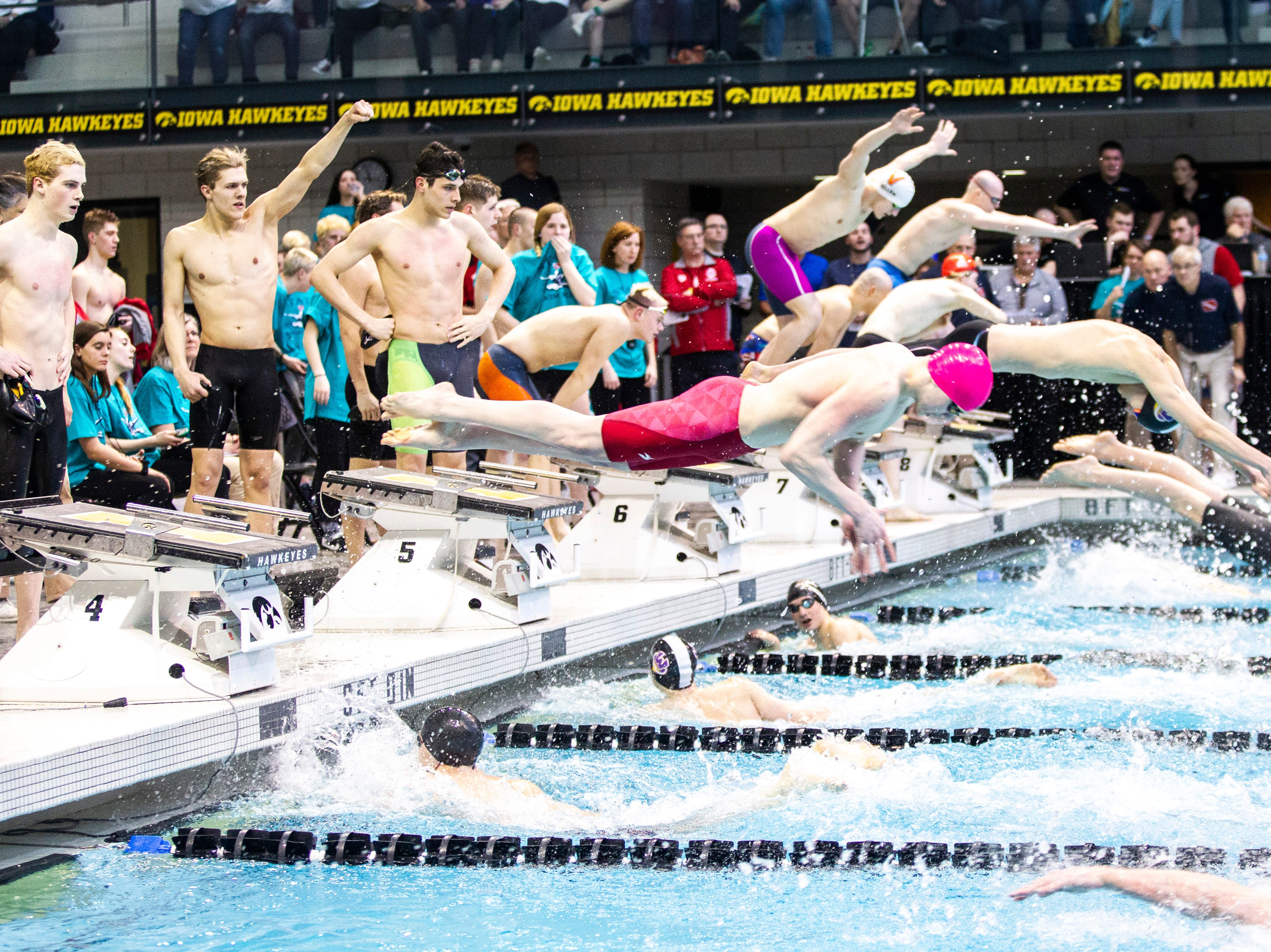 Competitors leap into the pool in the 200 yard freestyle relay during the Iowa boys' state swimming regional championship meet on Saturday, Feb. 9, 2019 at Campus Recreation and Wellness Center on the University of Iowa campus in Iowa City, Iowa.
