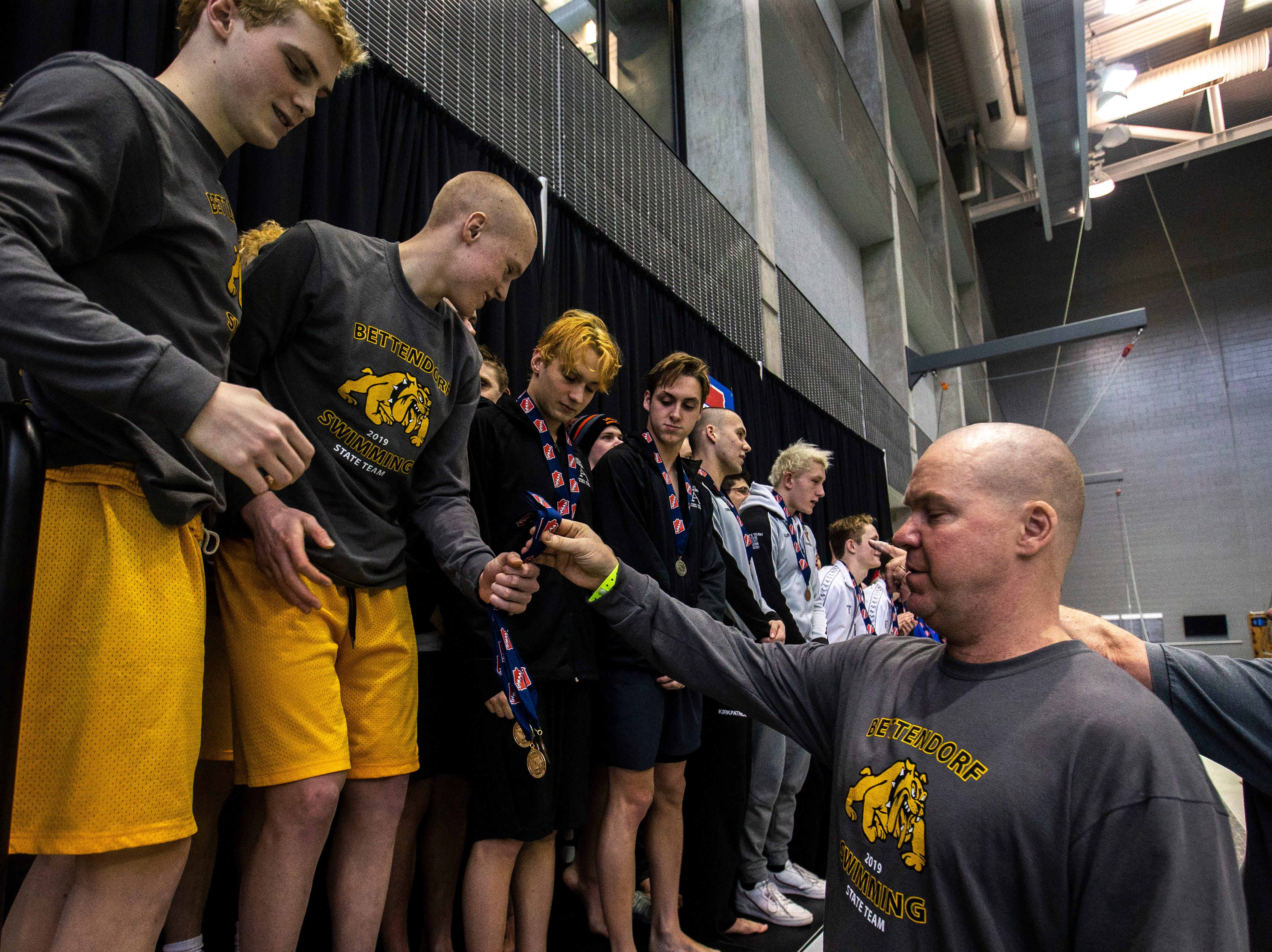 Bettendorf receives their first place medals for the 200 yard freestyle relay during the Iowa boys' state swimming regional championship meet on Saturday, Feb. 9, 2019 at Campus Recreation and Wellness Center on the University of Iowa campus in Iowa City, Iowa. Bettendorf finished first overall, with a time of 1:23.56.