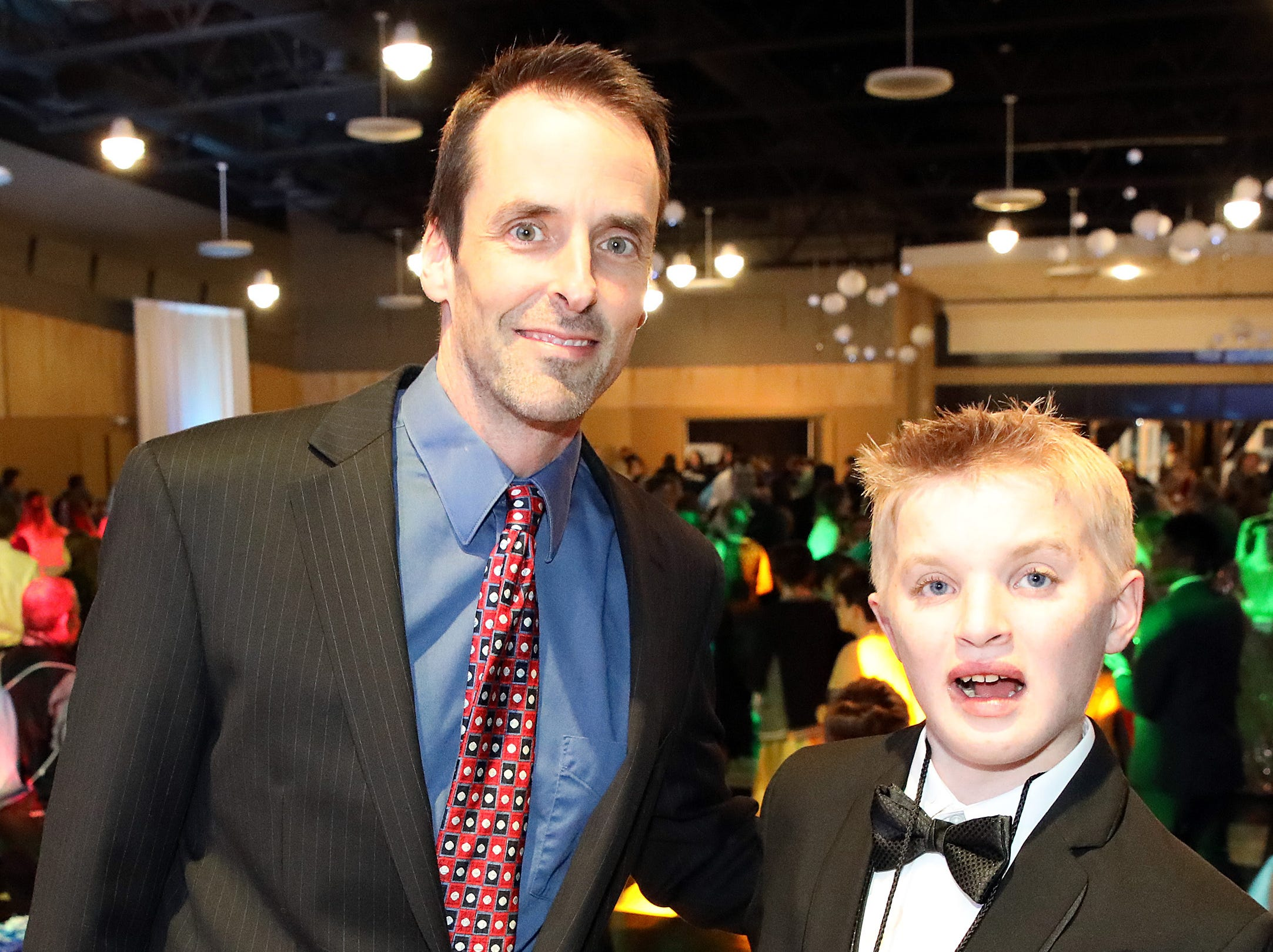The Rev. Mike Van Rees and Aspen Essink stop for a photo during the Night to Shine event at Prairie Ridge Church in Ankeny on Friday, Feb. 8, 2019. Sponsored by the Tim Tebow Foundation, the event for adults with special needs features a prom-like atmosphere with dancing, limo rides, food and more.