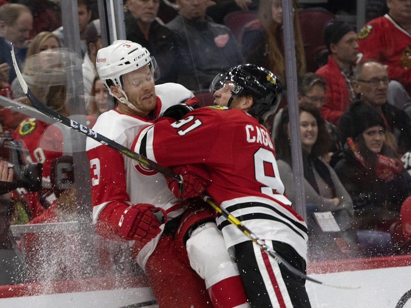 Chicago Blackhawks center Drake Caggiula slams Detroit Red Wings defenseman Nick Jensen into the boards during the first period on Sunday, Feb. 10, 2019, at the United Center in Chicago.