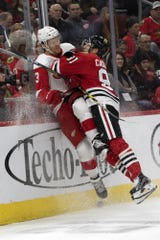 Blackhawks center Drake Caggiula slams Nick Jensen into the boards Feb. 10.