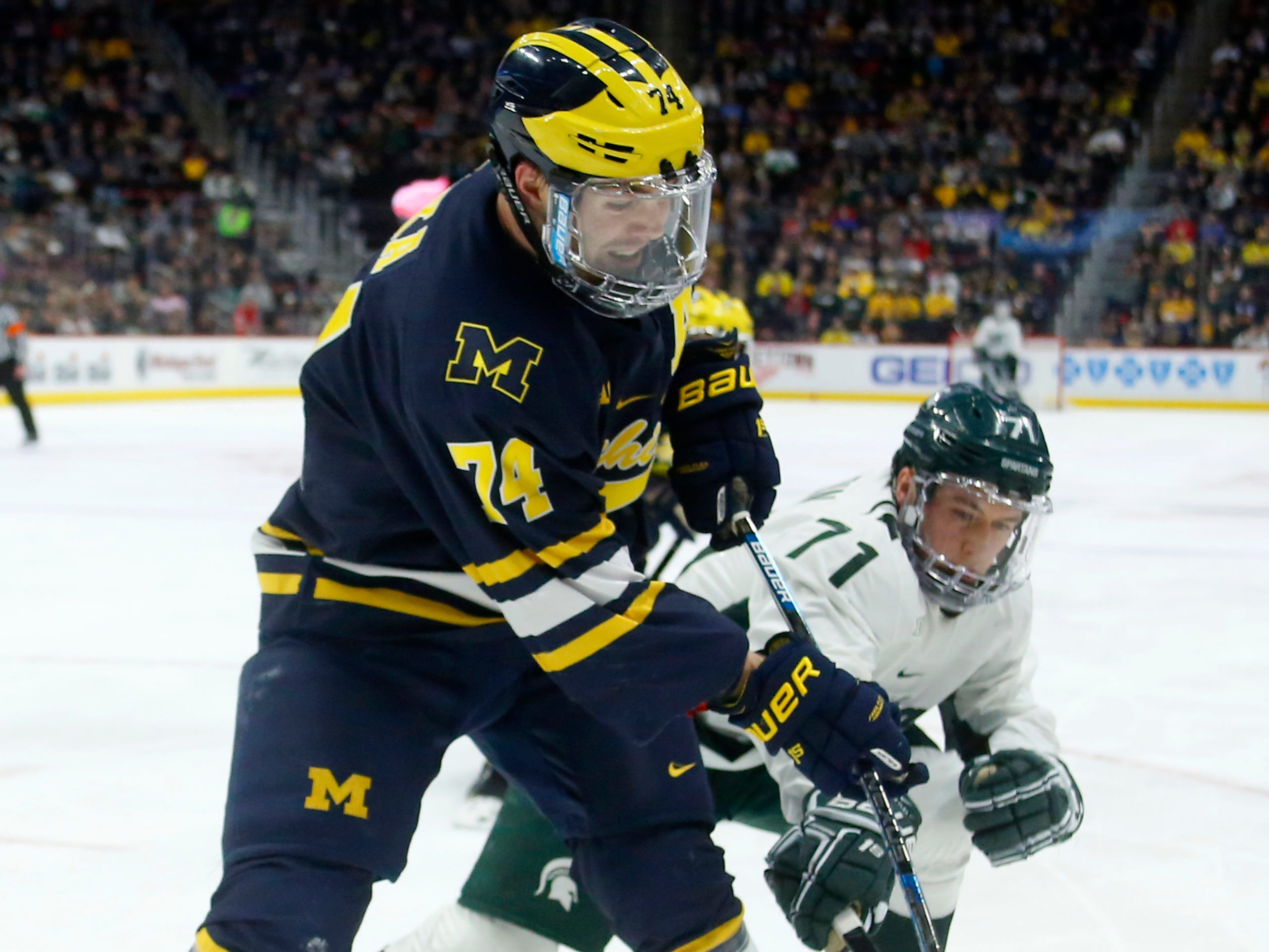 Michigan State forward Logan Lambdin tries to steal the puck from Michigan defenseman Nicholas Boka during the second period on Saturday, Feb. 9, 2019, at Little Caesars Arena.